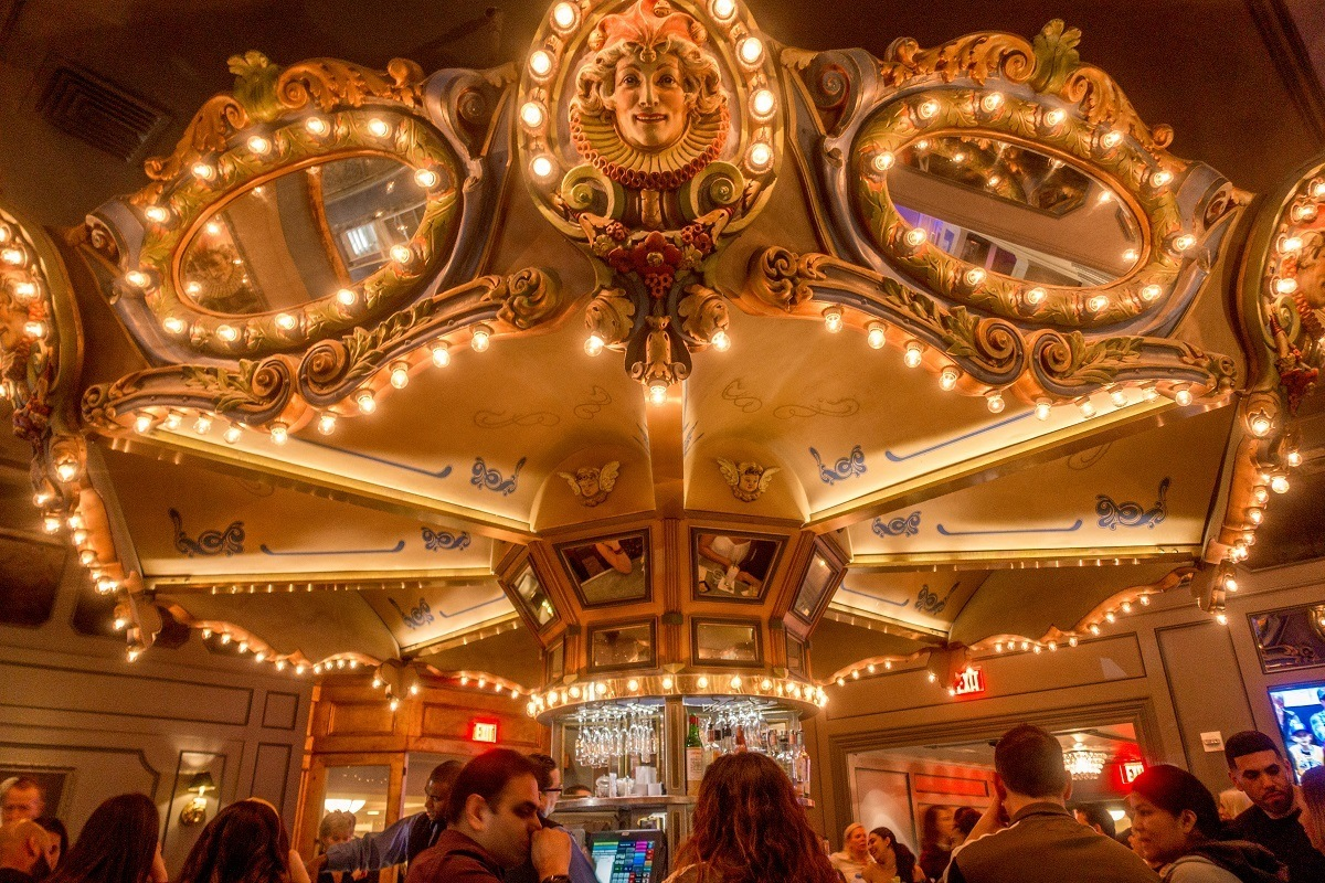 People sitting at the circular Carousel Bar at night