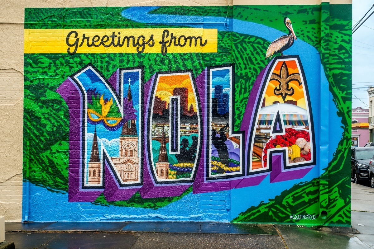 """Street art mural that says """"Greetings from NOLA"""" and features scenes from New Orleans"""