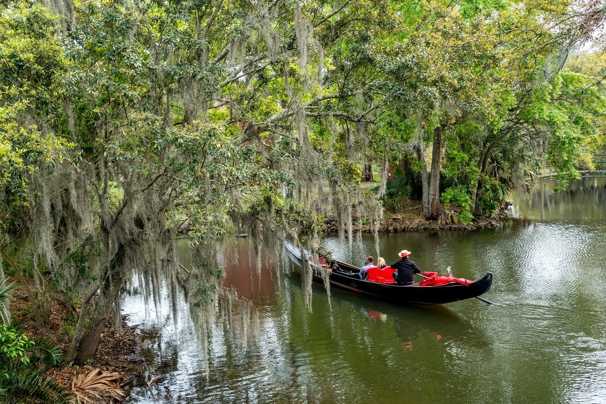 Venetian gondola in a lagoon surrounded by moss-draped trees