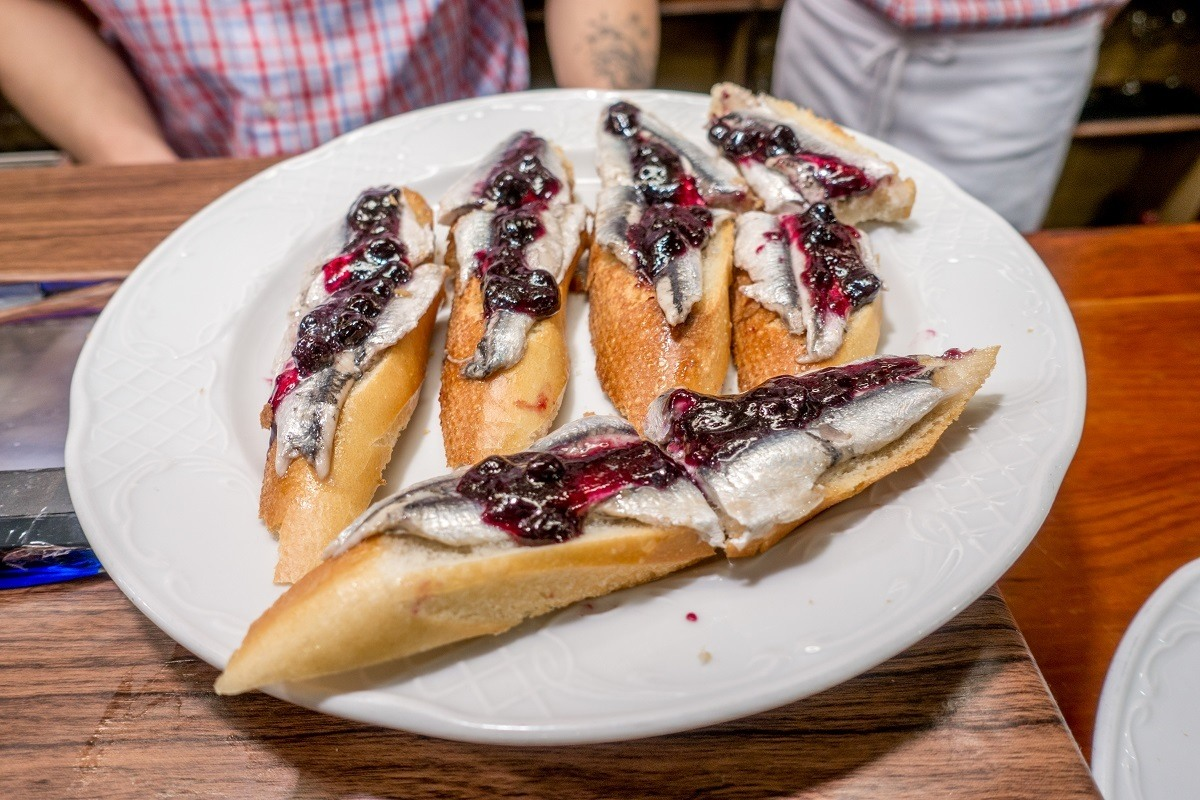 Anchovies topped with blueberry jam on a plate