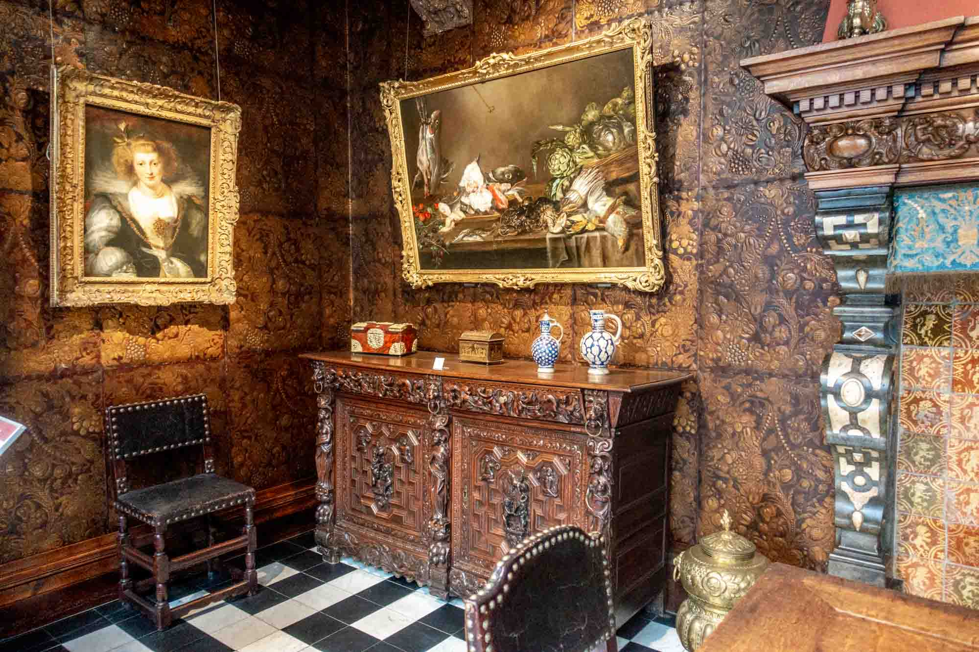 Room with paintings, furniture, and elaborate wall coverings