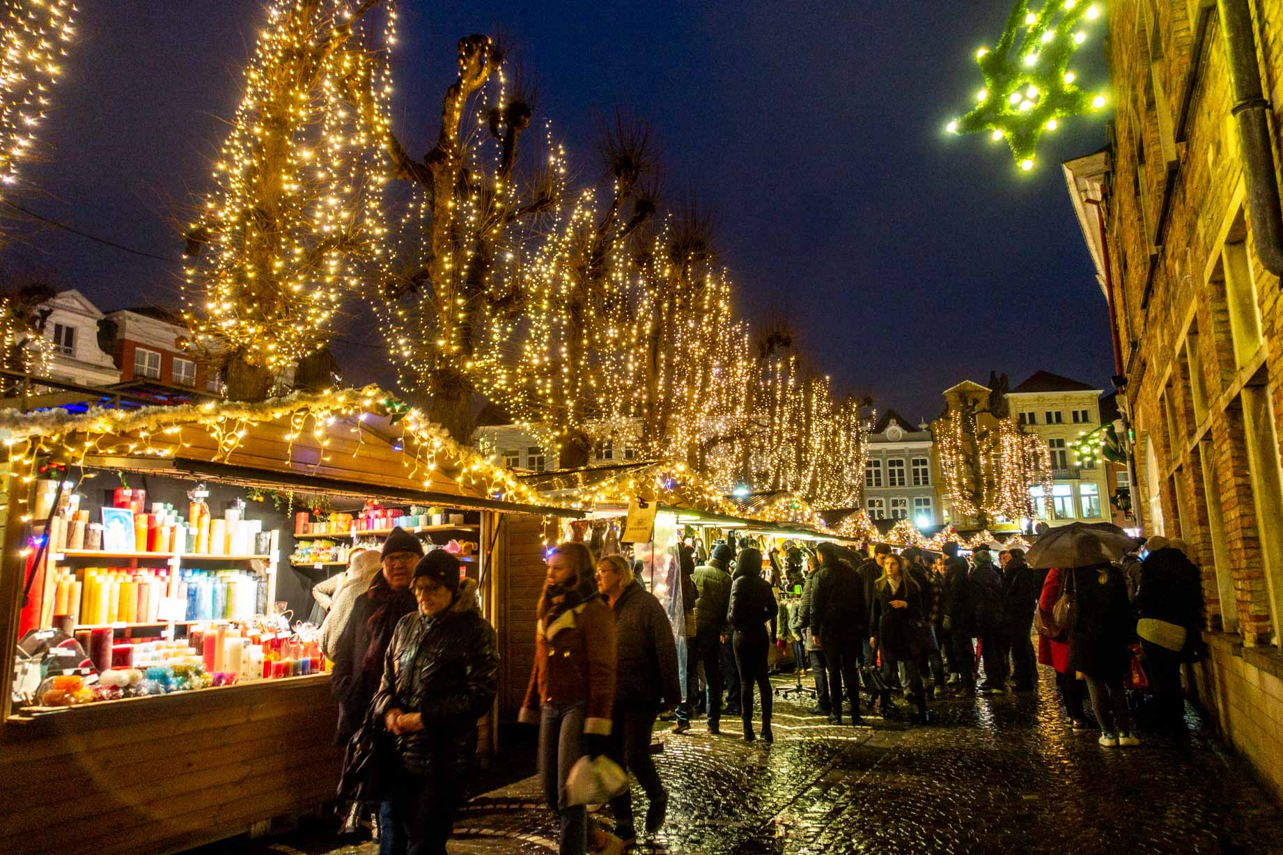 Shoppers at the market stalls decorated with Christmas lights