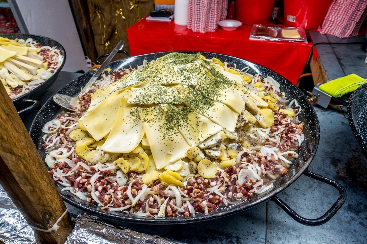 A dish of potatoes, cheese, lardons, onions, and wine