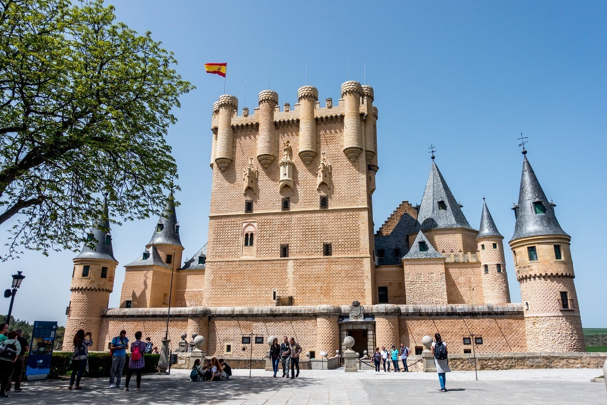 Exterior of a castle with turrets and Spanish flag