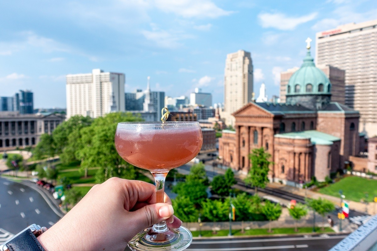Cocktail glass in front of a skyline view of a church and buildings