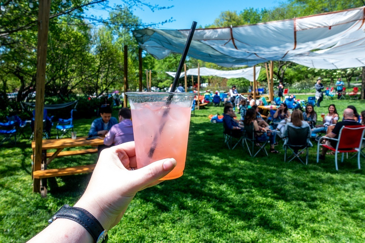 Pink drink in front of a group of people in the park