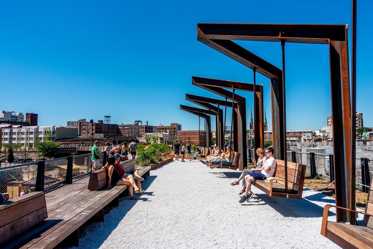 People sitting on swings and benches at an elevated park