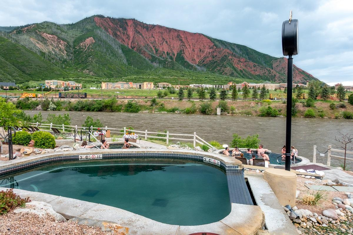 Hot springs pool near a river with red mountain in background