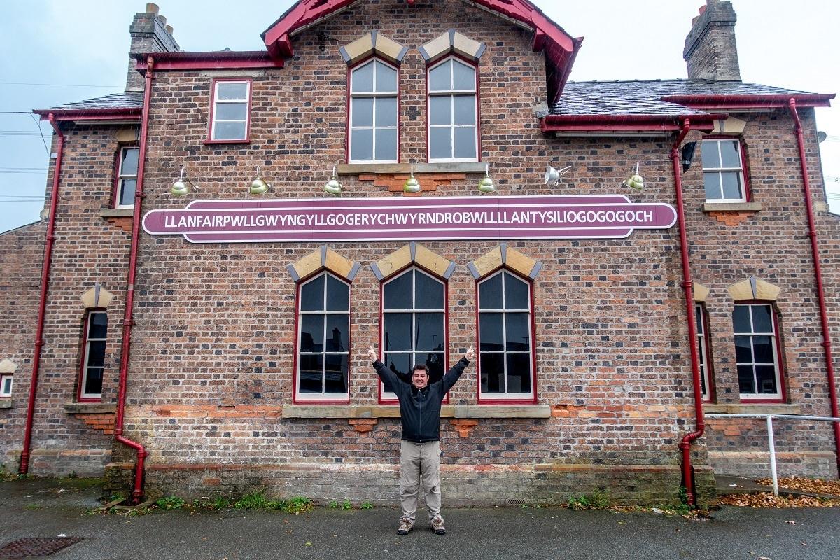 Person in front of a brick building with a sign for Llanfairpwllgwyngyllgogerychwyrndrobwllllantysiliogogogoch