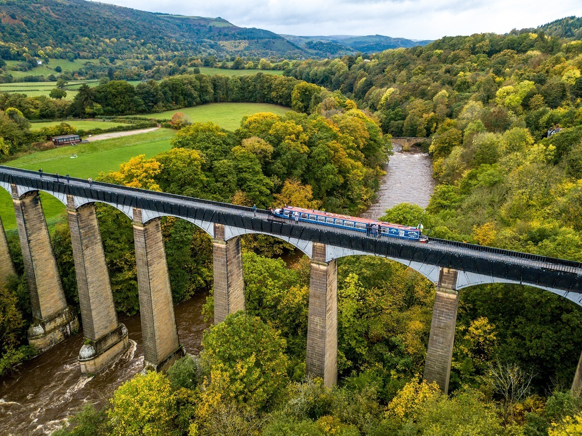 Aerial photo of a boat in Pontcysyllte Aqueduct which crosses the river below