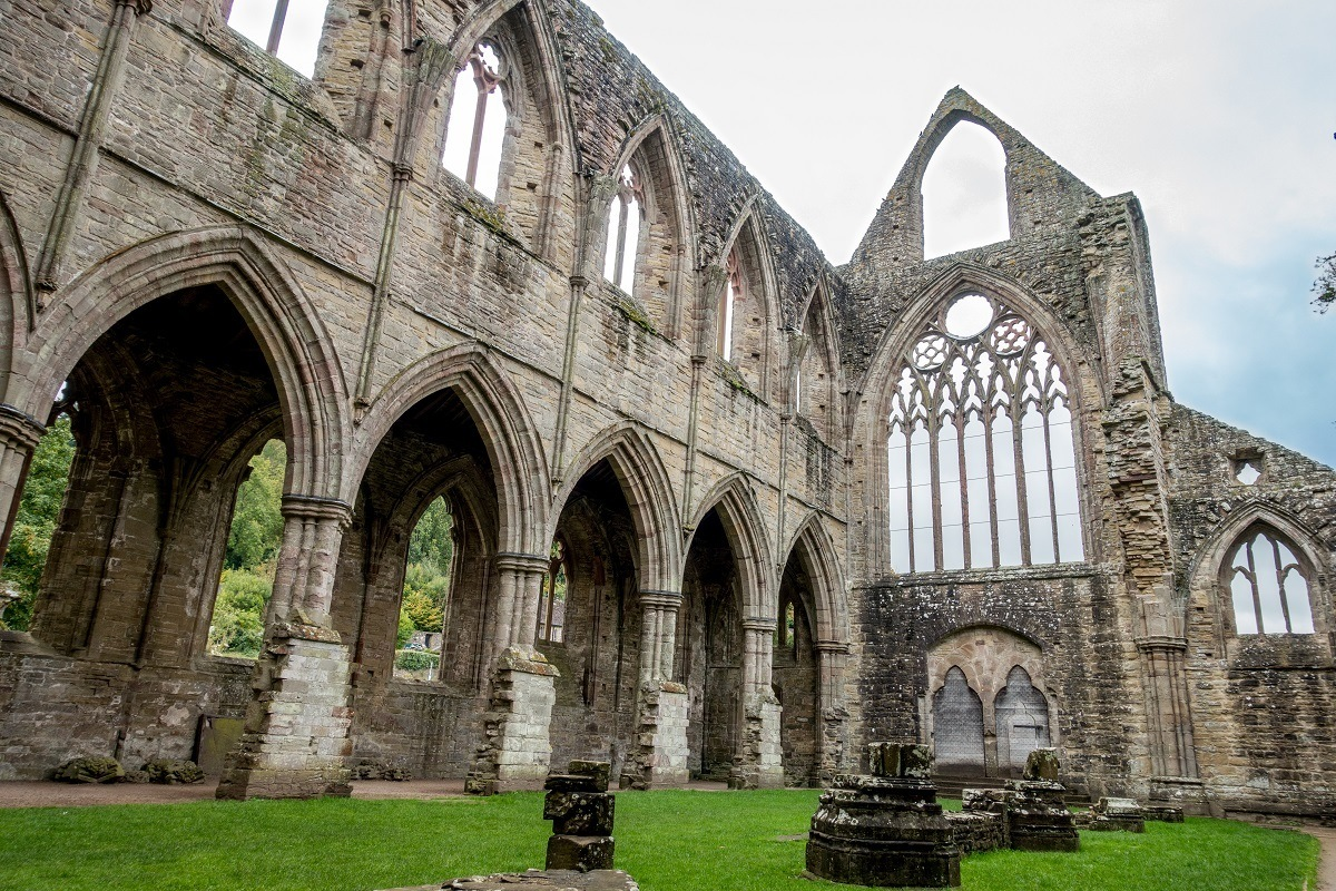 Ruins of a stone church with arches and intricate window frames