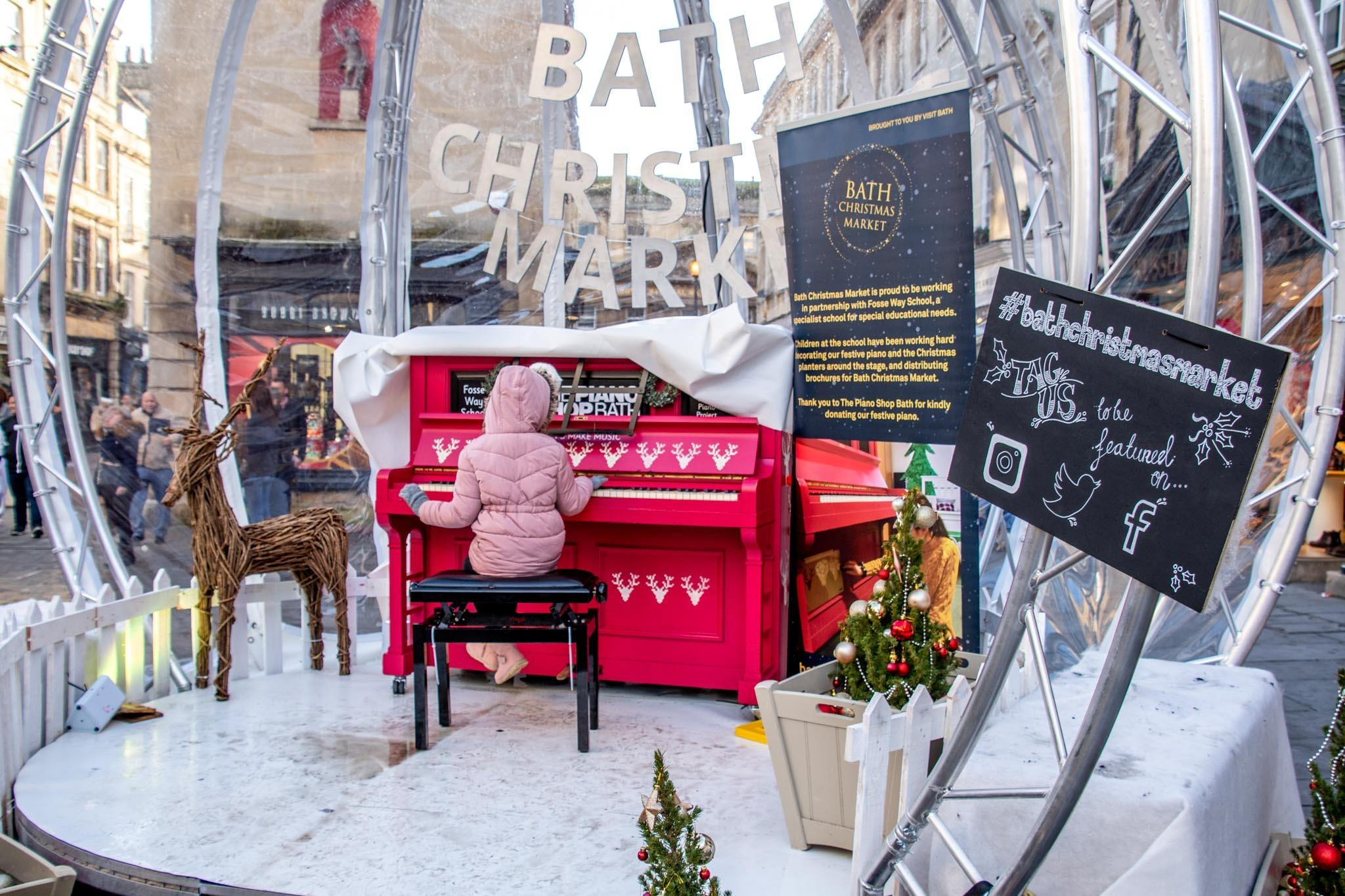 Girl in pink coat playing piano outside