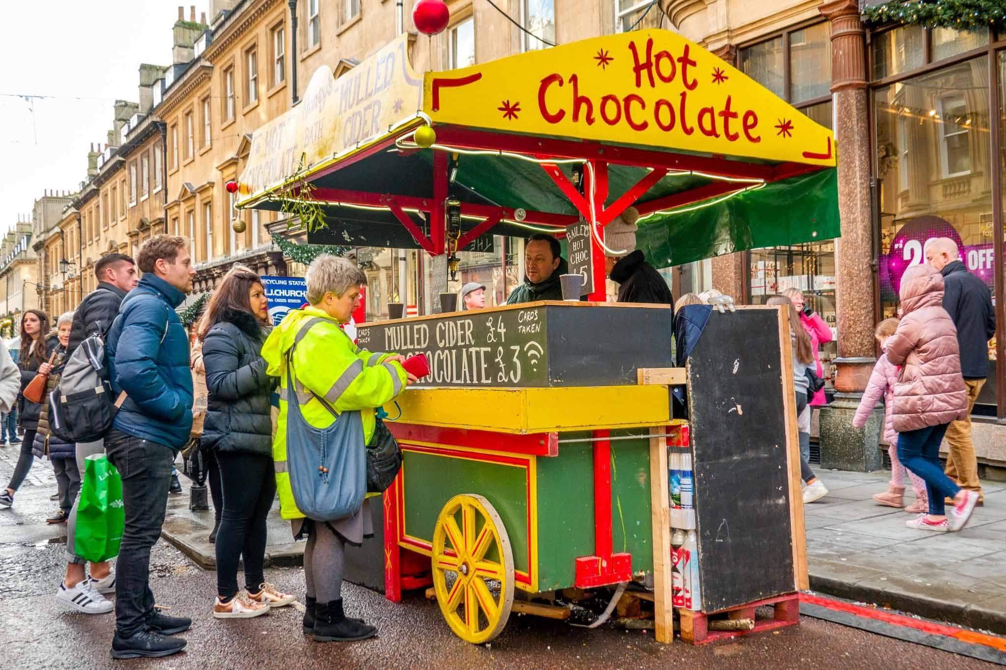People standing at yellow and green hot chocolate cart in the street