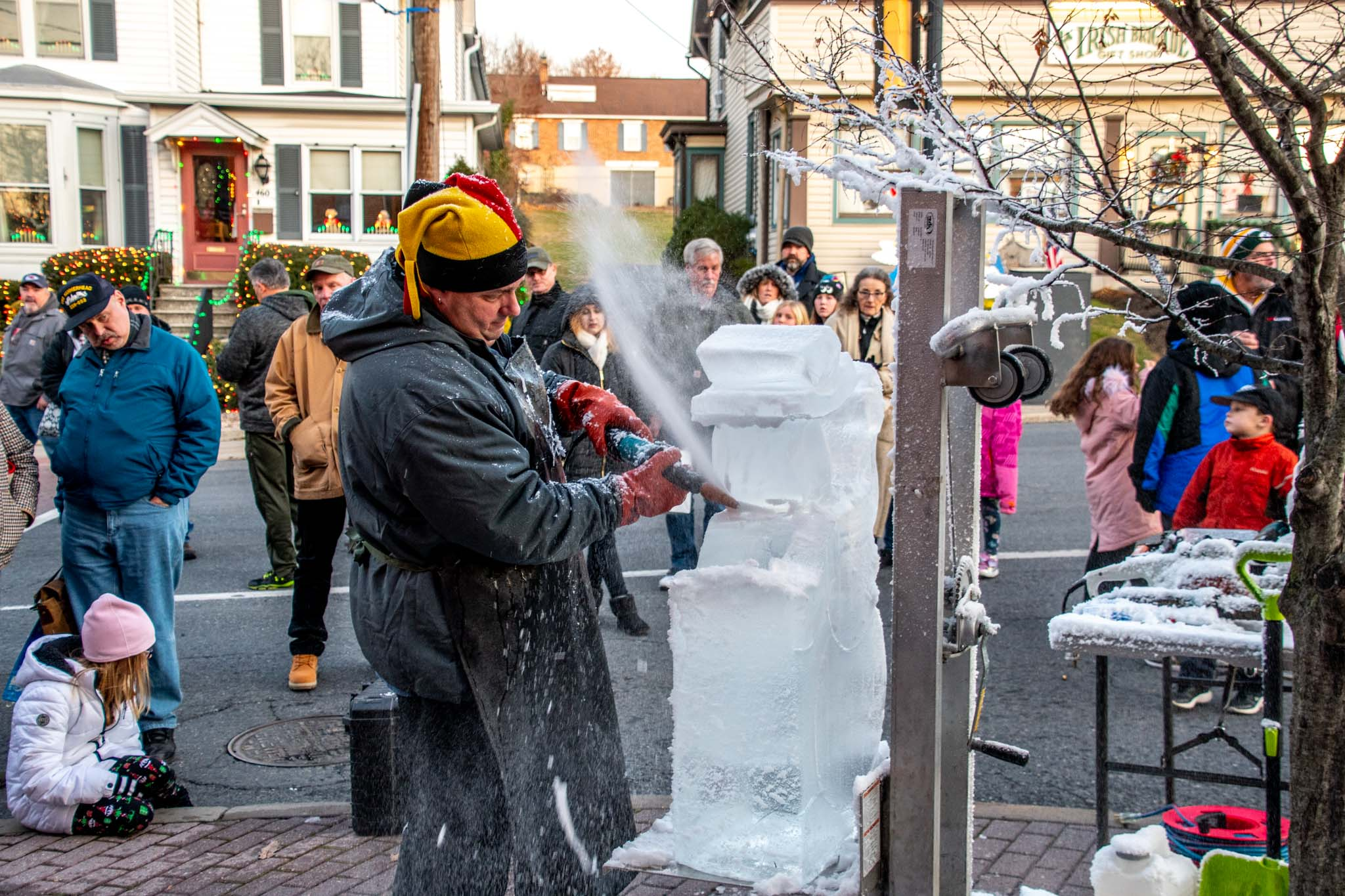 Man carving ice block into a snowman with a crowd looking on