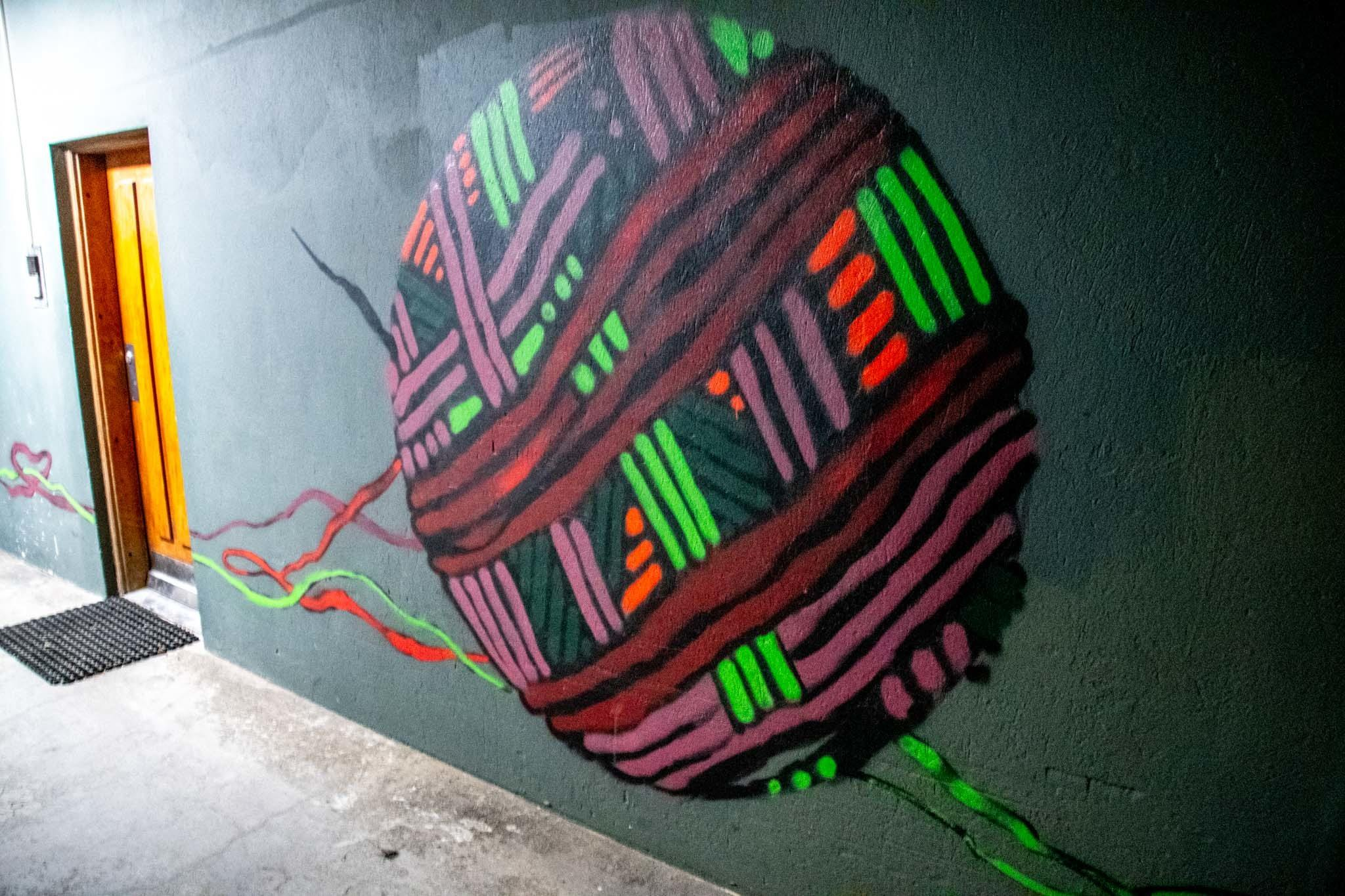 The ball of string is part of a two-part opposing mural