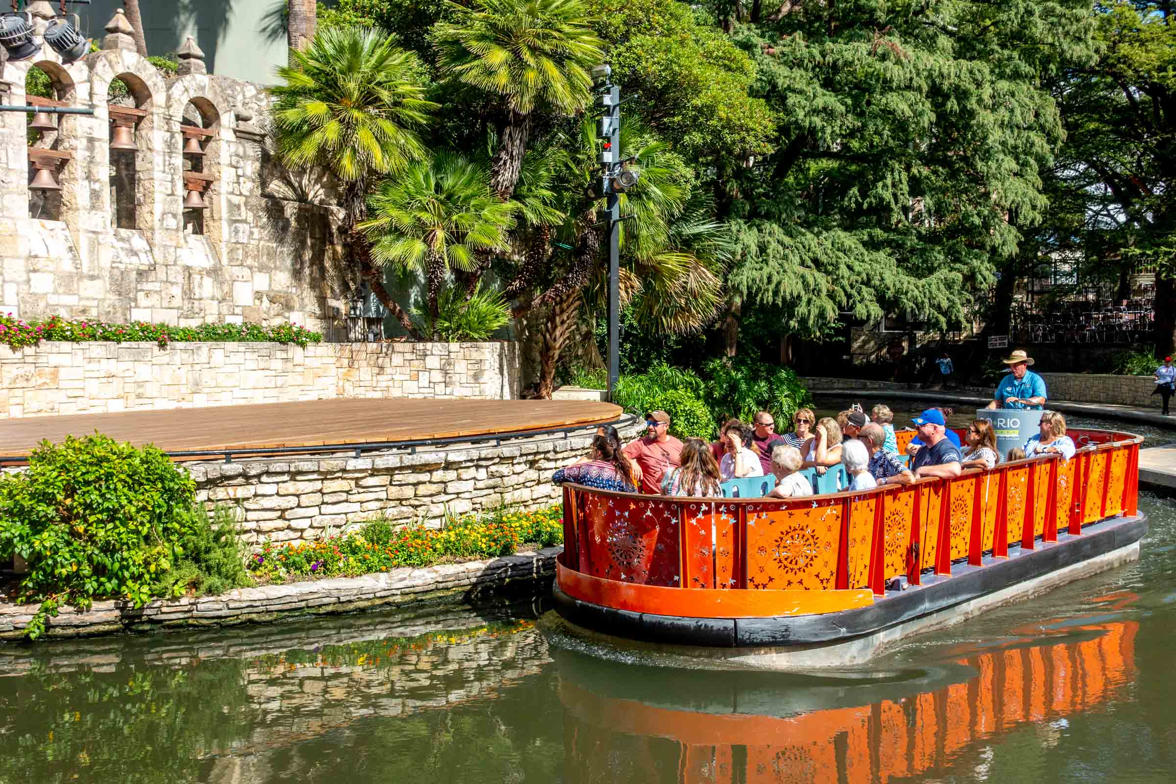 Orange boat filled with people in river