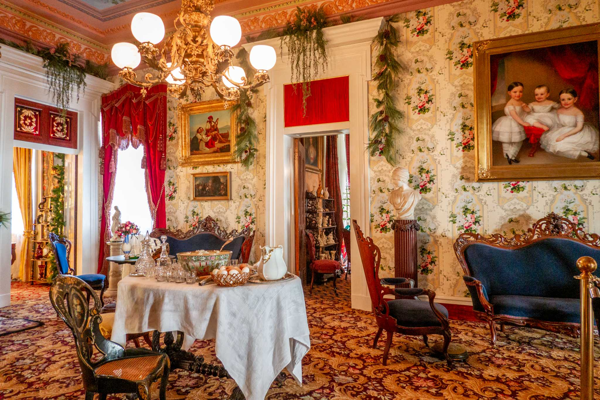 Room with table, chairs, a portrait, and decorations
