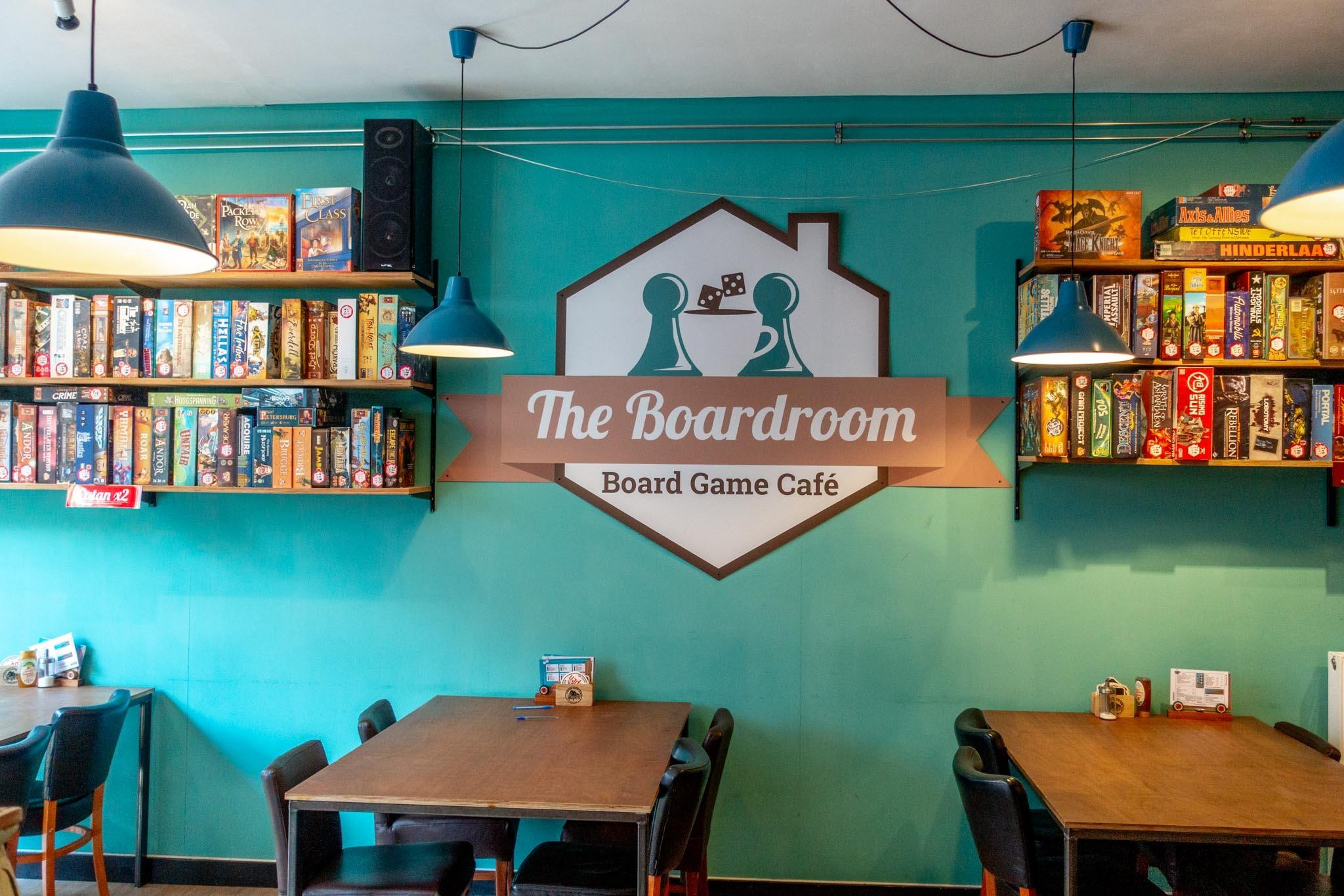 Interior of a cafe with tables, chairs, and boardgames on shelves
