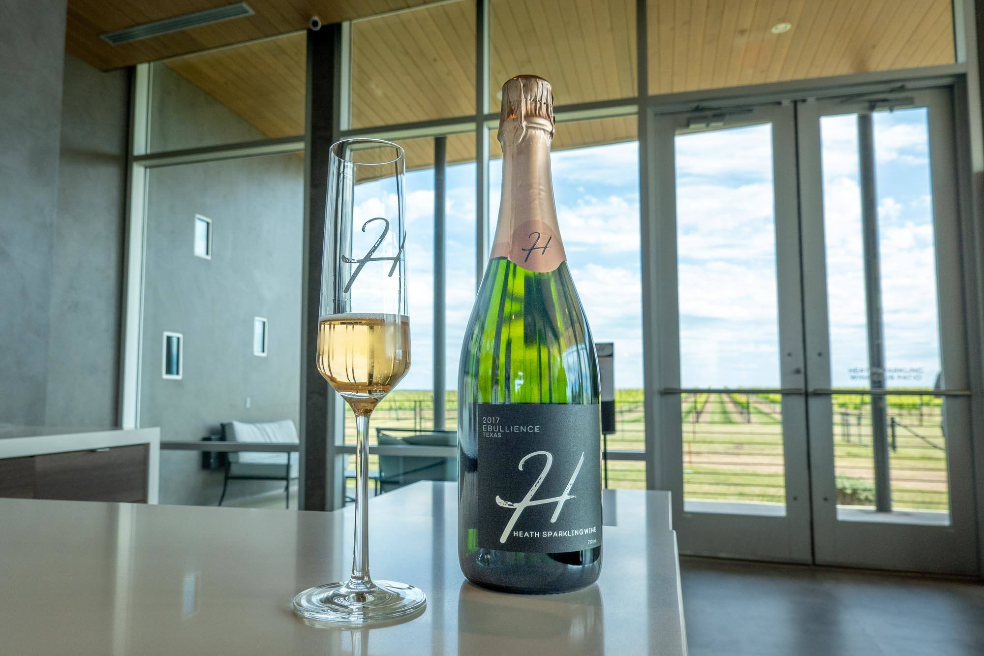 Glass and bottle of sparkling wine on a counter with a view of grapevines outside