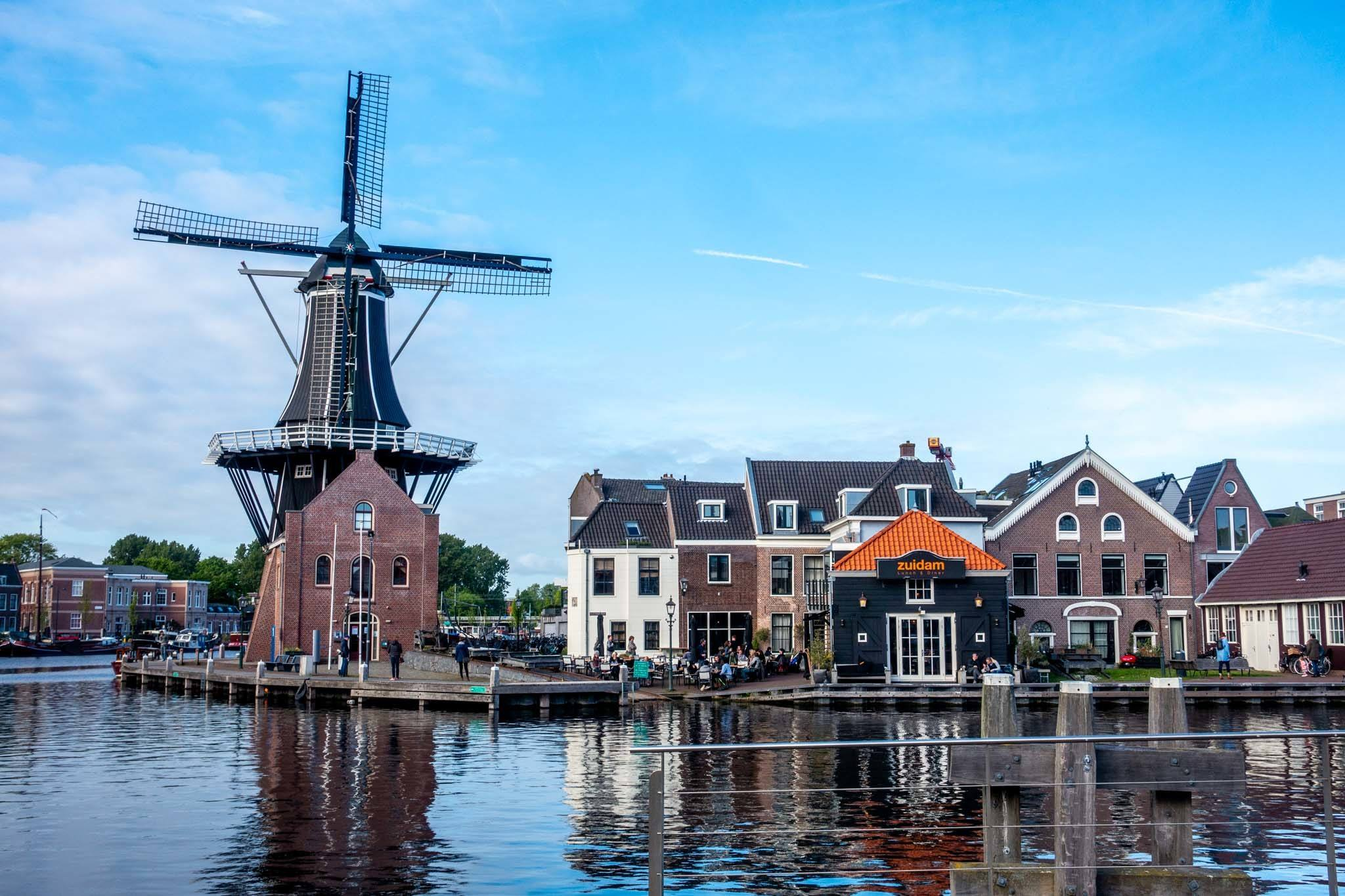 Windmill and buildings overlooking a river