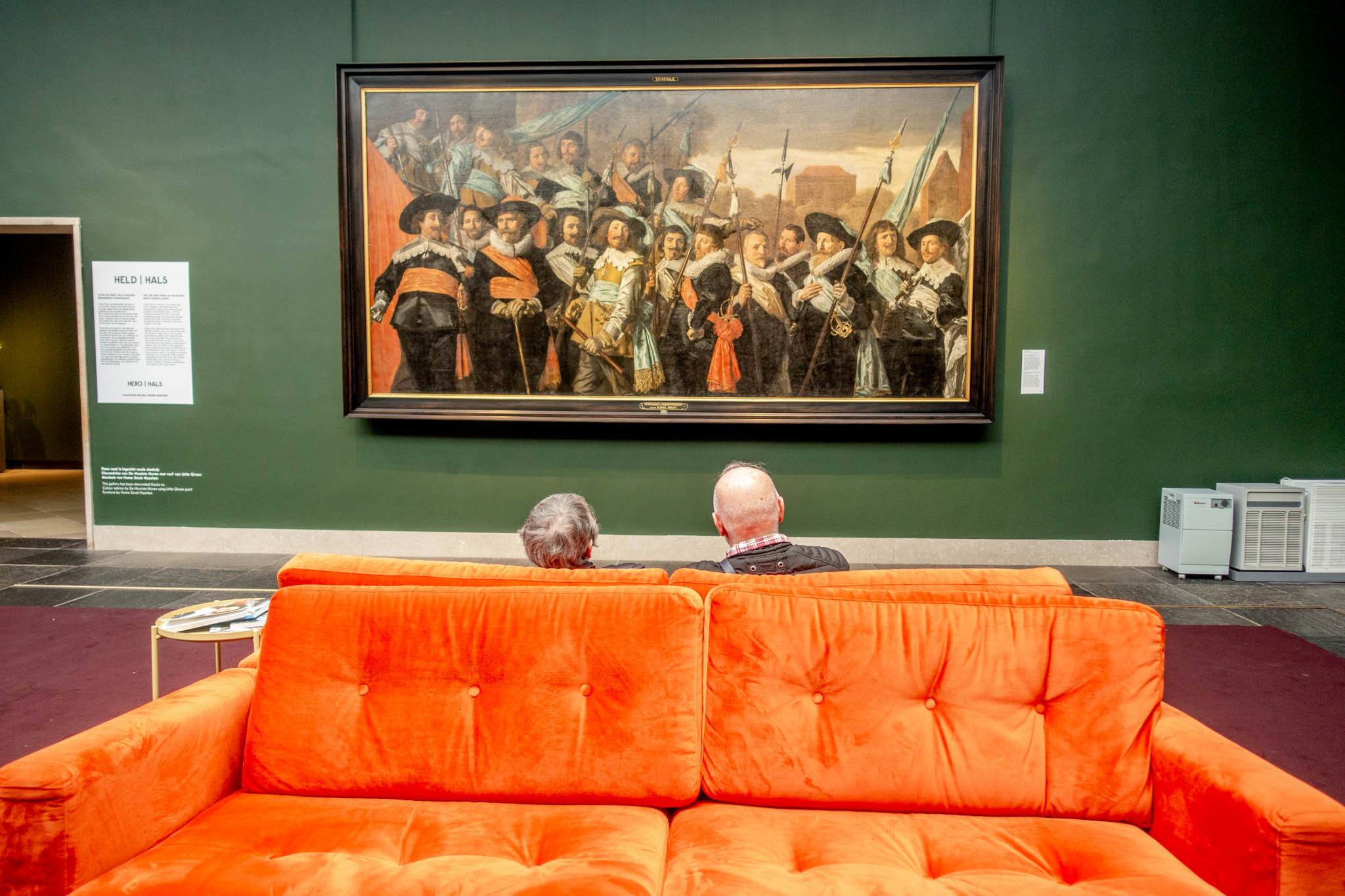 Couple seated on orange couch looking at artwork on green wall at Frans Hals Museum