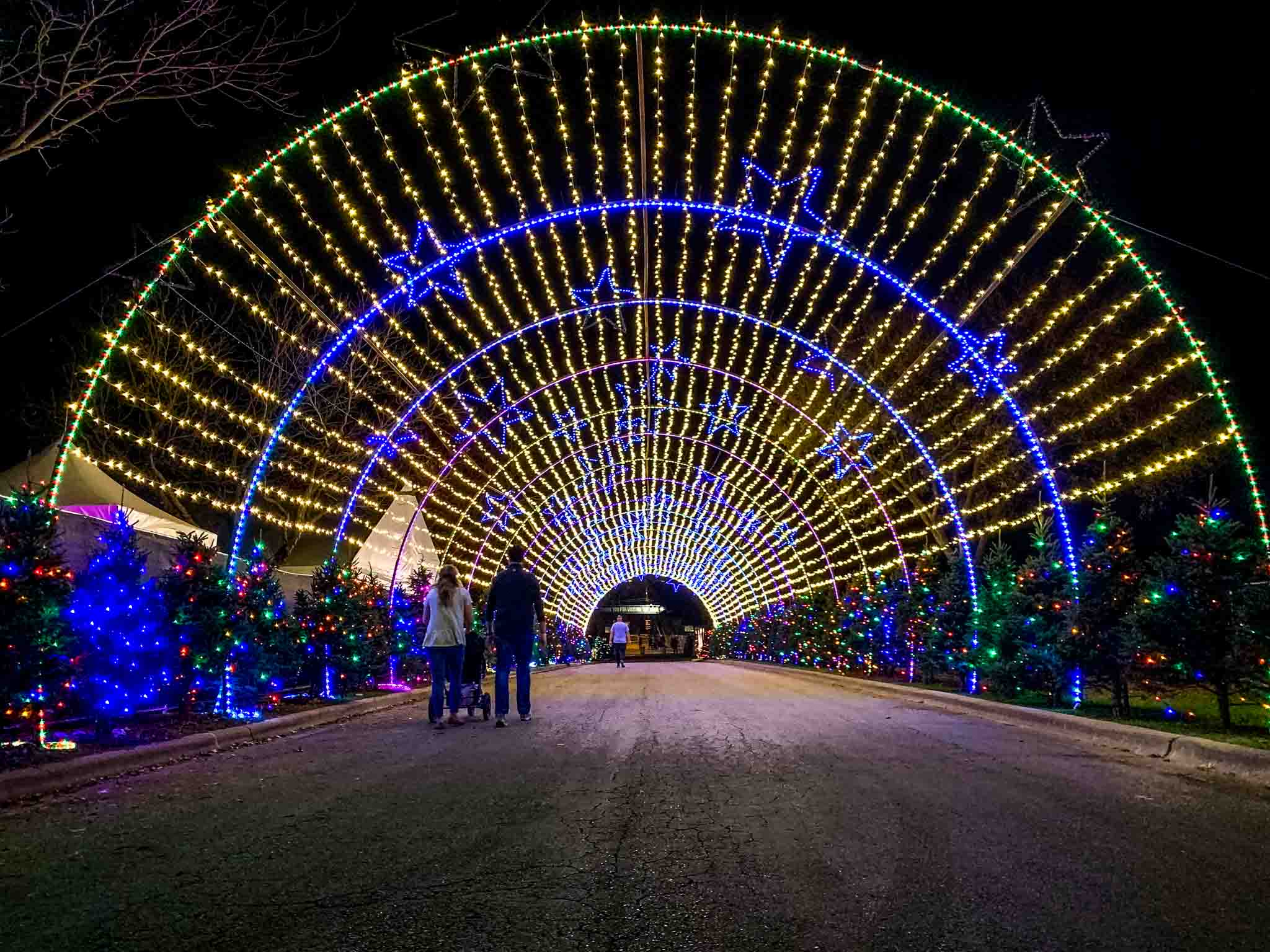 People walking through a tunnel of Christmas lights at night