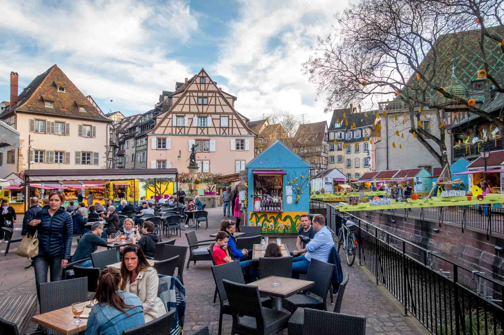 People having drinks outdoors with a spring market in the background