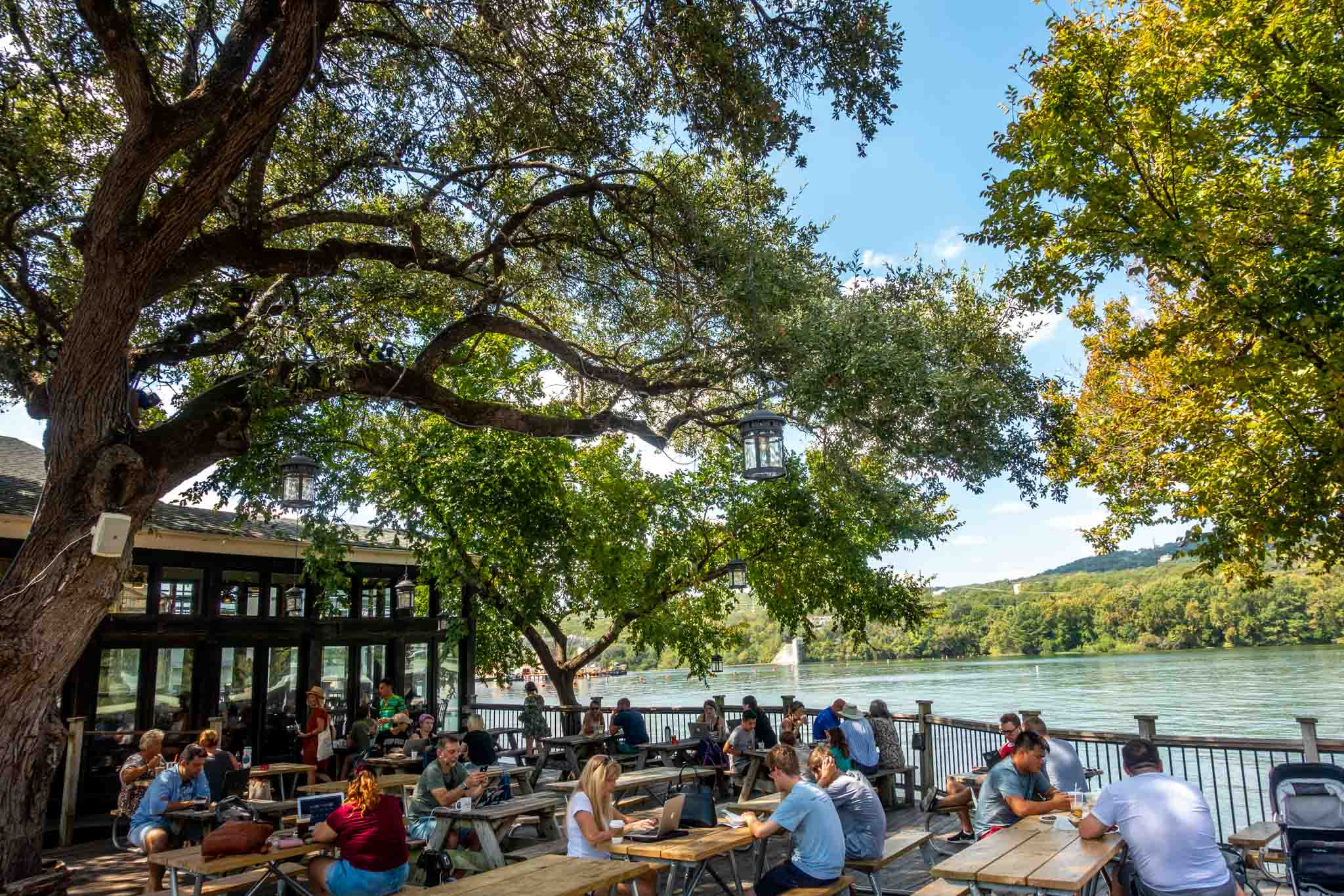 People sitting at picnic tables on a patio by a lake