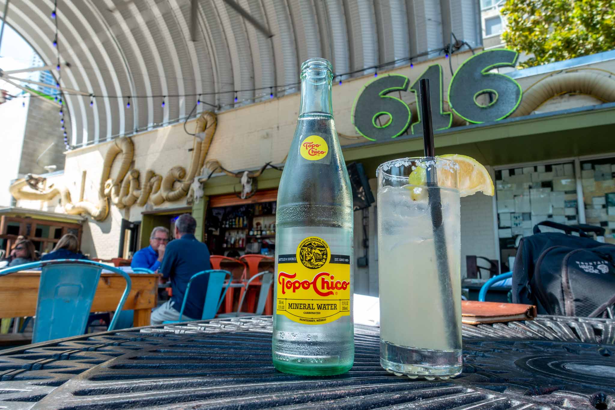 Bottle of Topo Chico next to a glass with a slice of lime