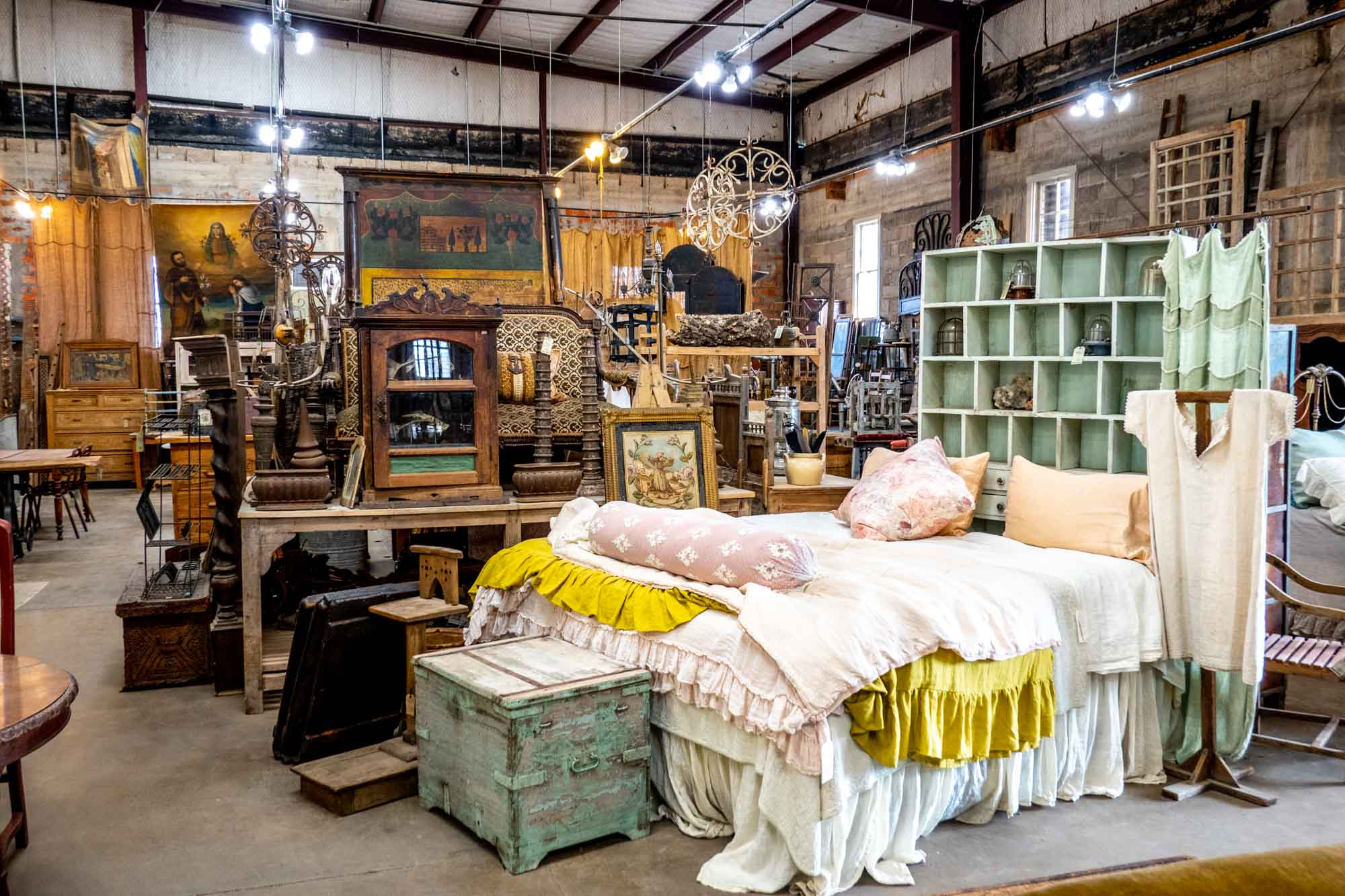Bed and an assortment of antiques in a showroom