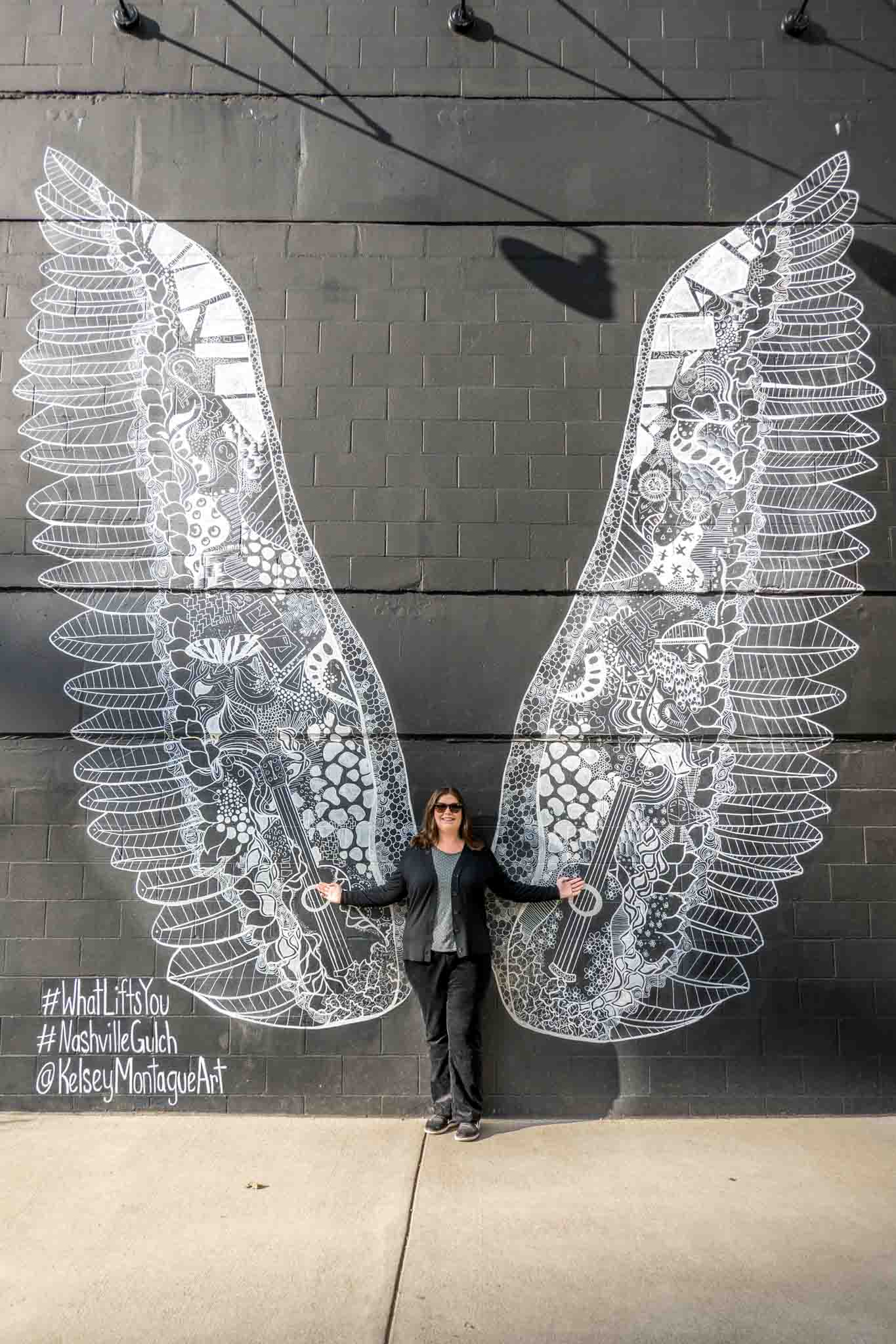 Person posing with mural of large white wings