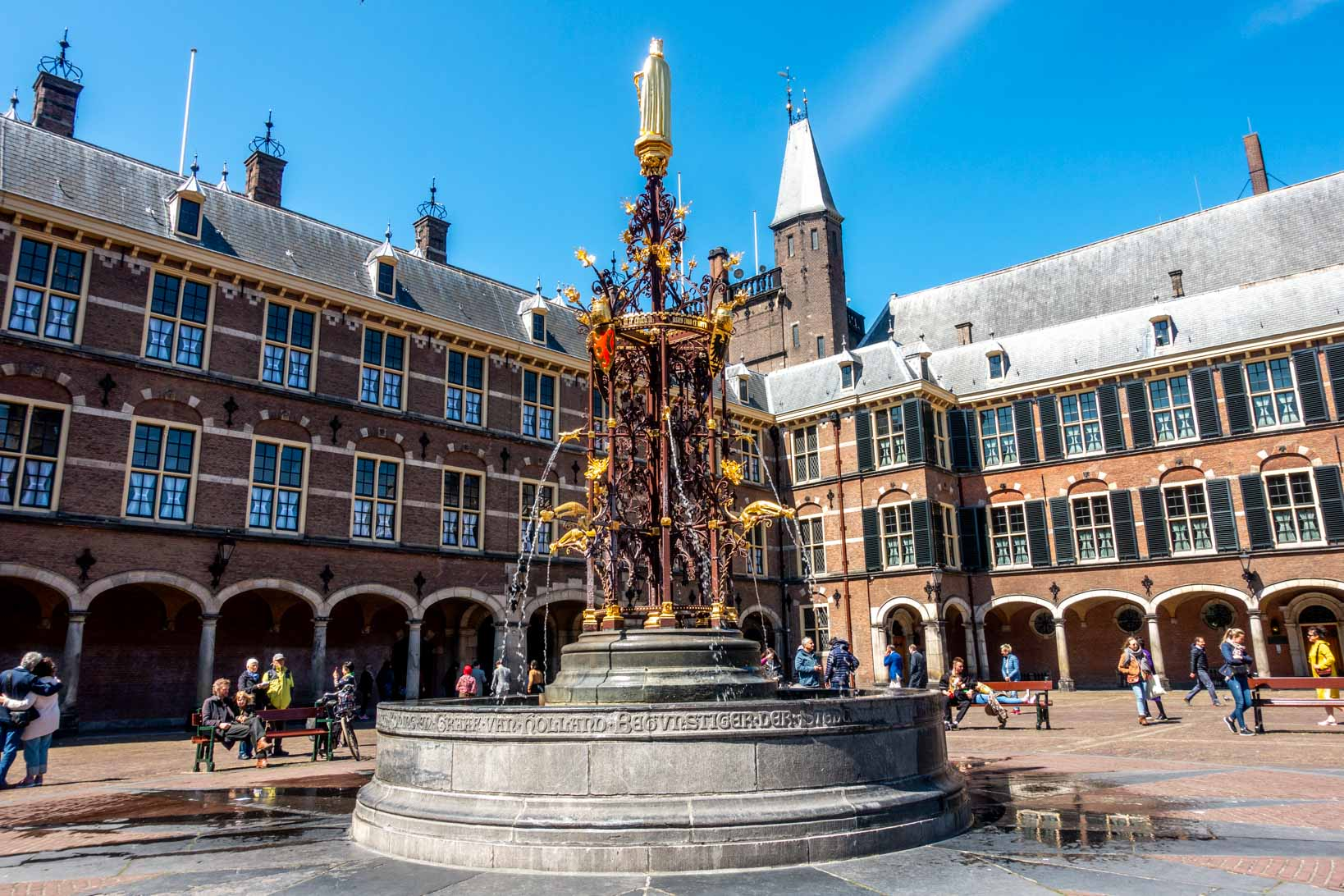 Gold ornametal fountain in a courtyard surrounded by a building