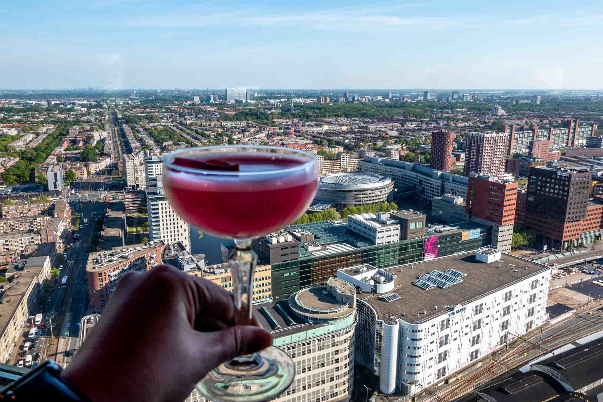 Person holding a cocktail overlooking a city skyline
