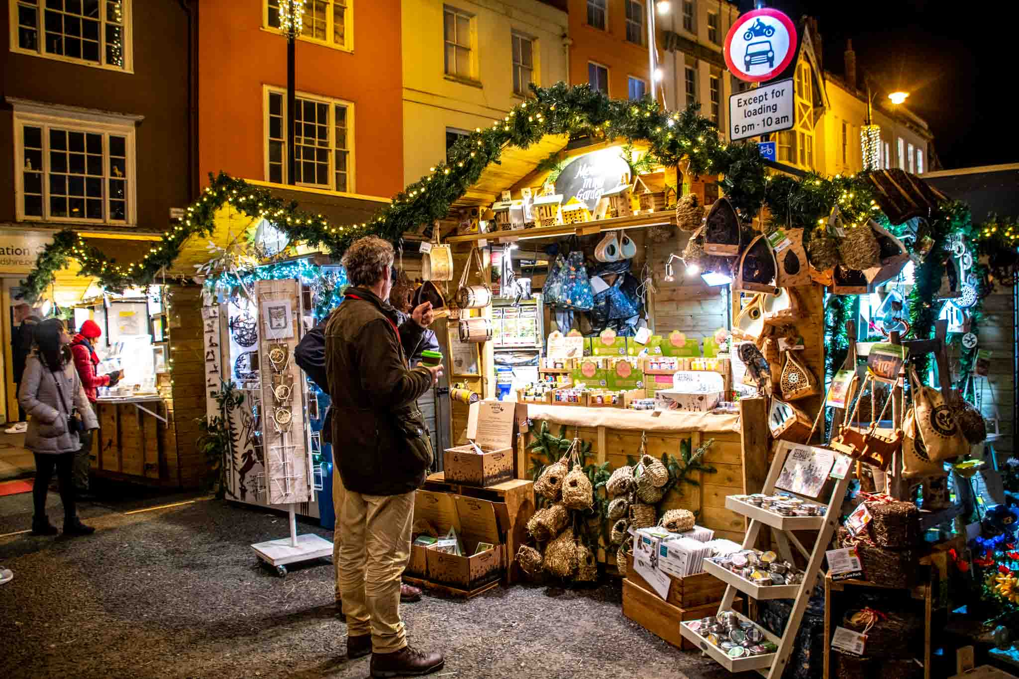 Shoppers in front of wooden chalets selling Christmas gifts