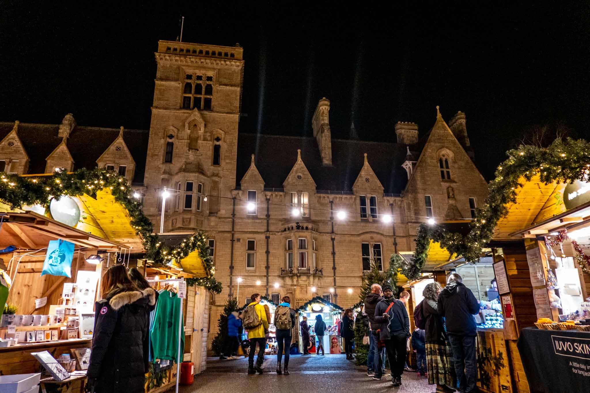 People shopping at Christmas market stalls at night