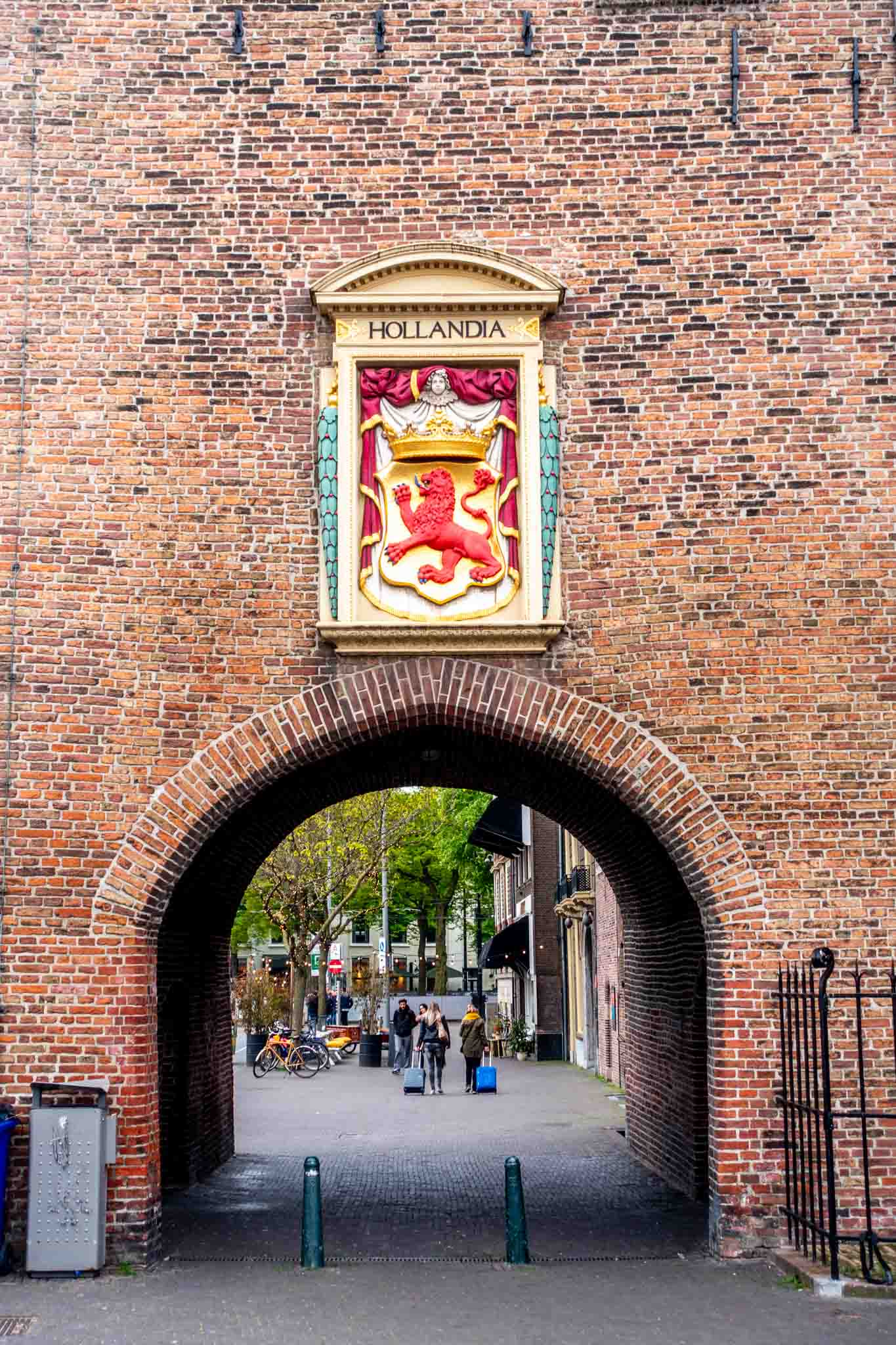 """Coat of arms and sign for """"Hollandia"""" hanging over a brick city gate"""