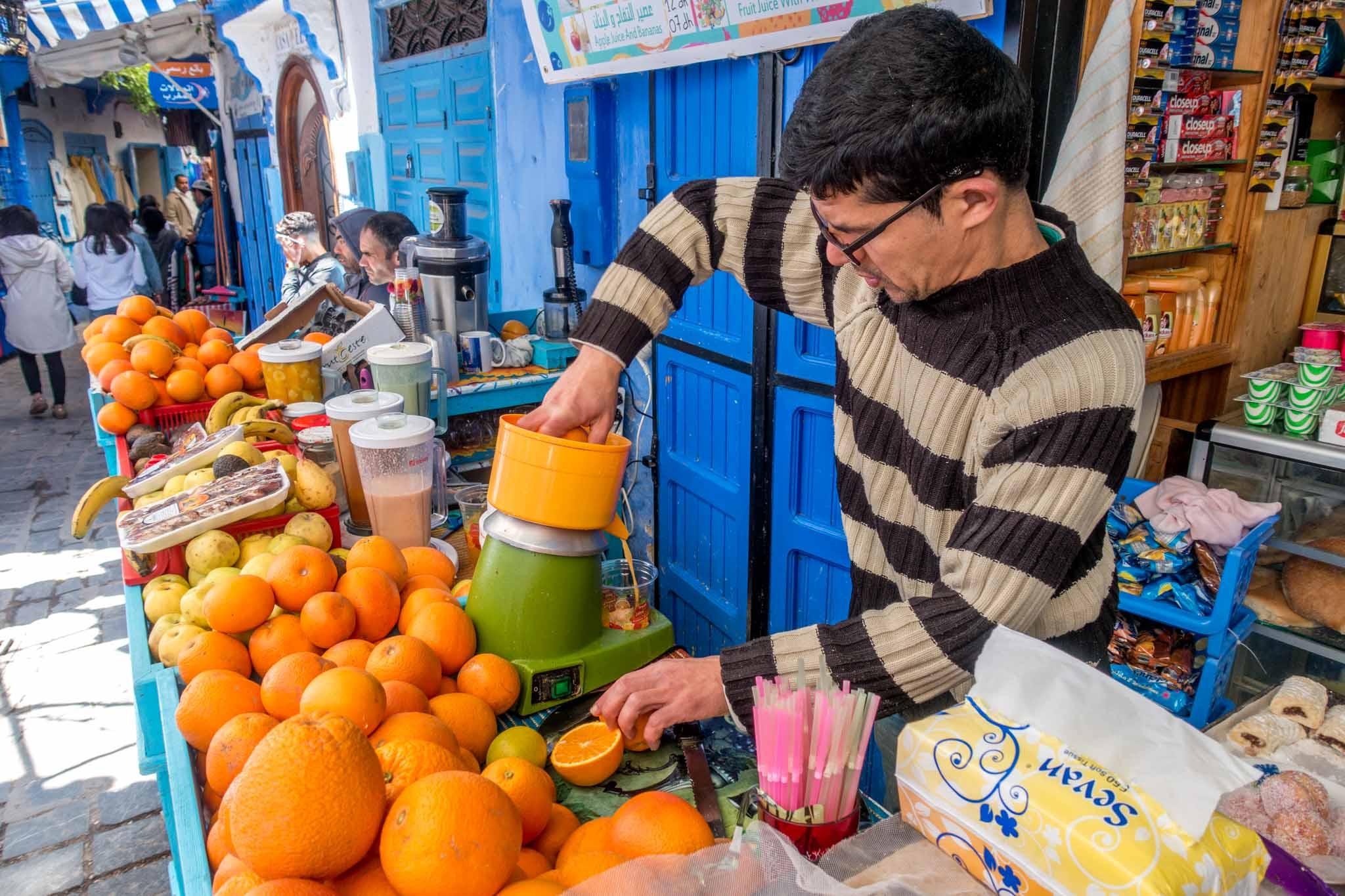 Man making fresh orange juice at a juice stand