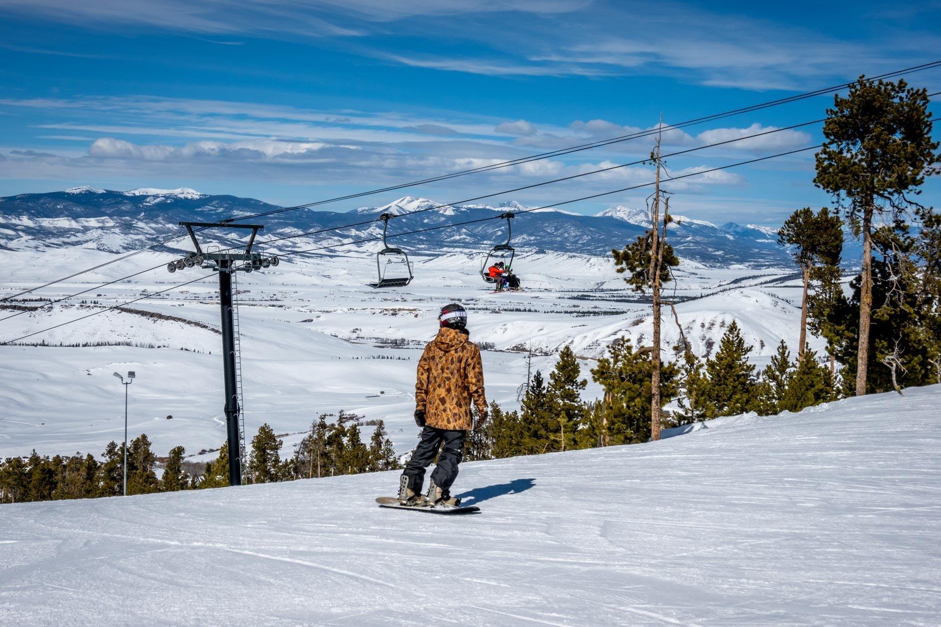 Snowboarder on a mountain near a ski lift
