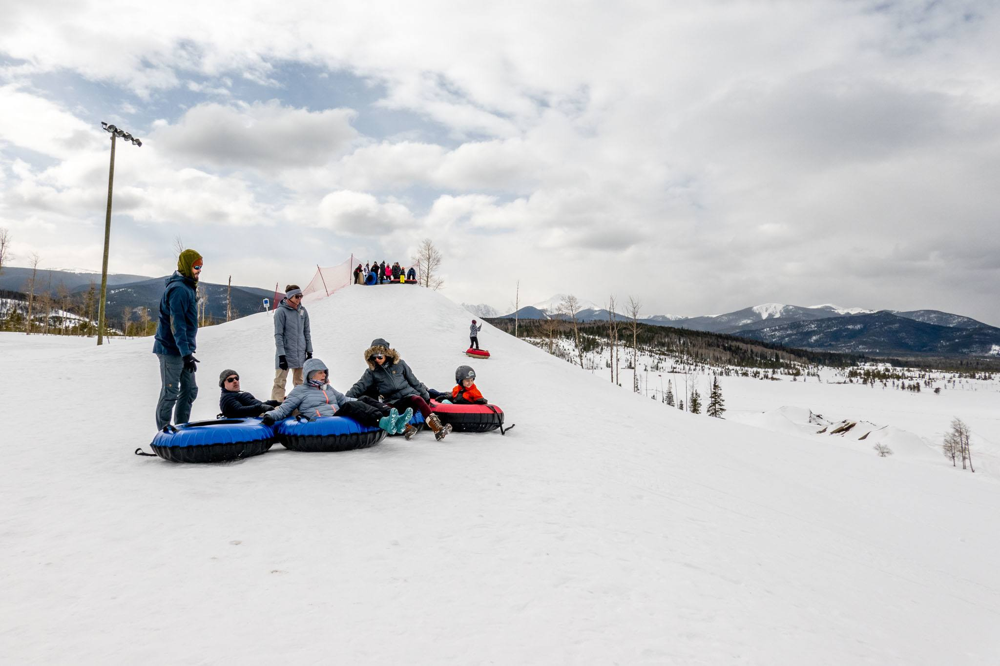 Group in innertubes at the top of a snow-covered hill