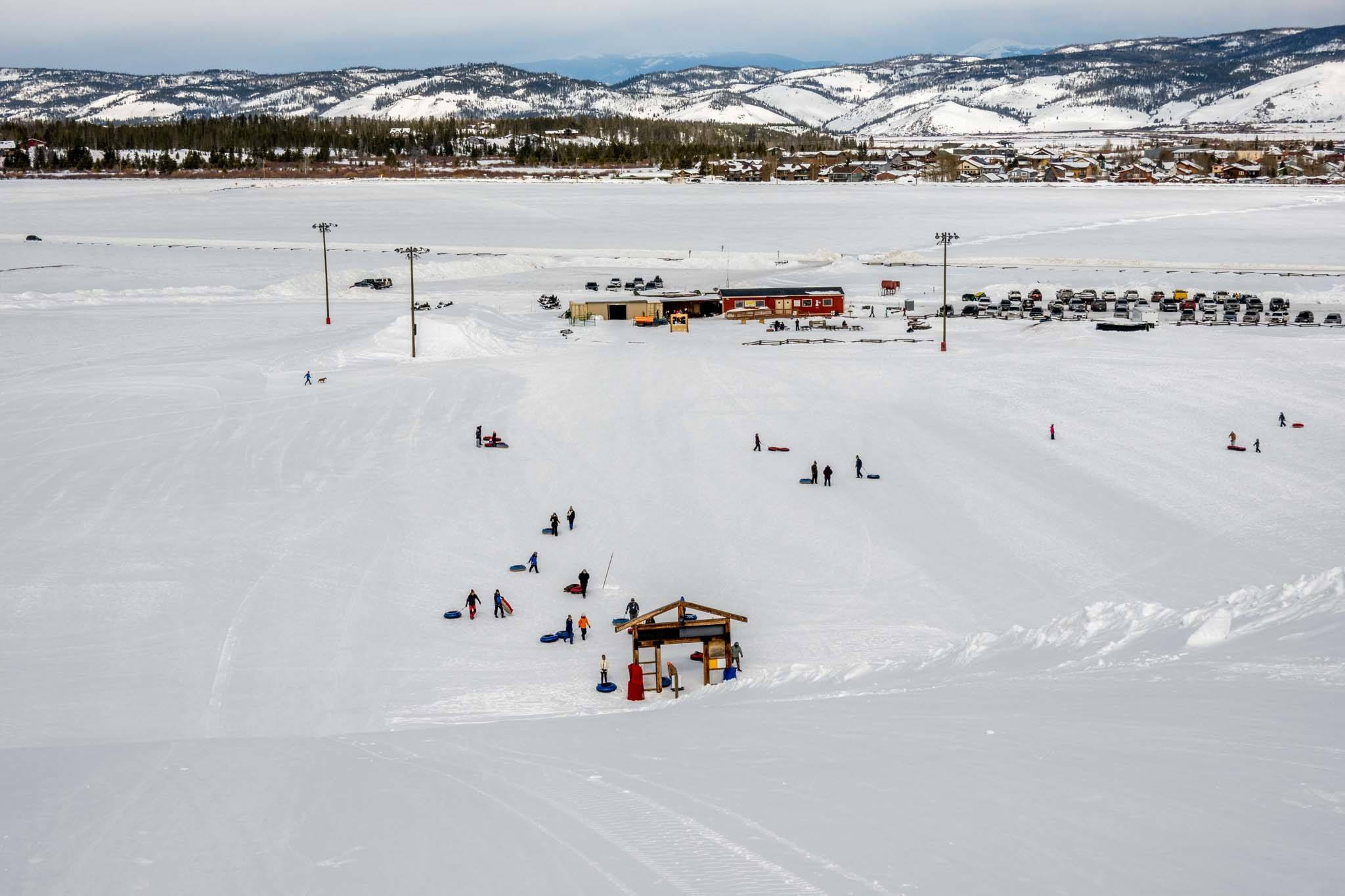 Snow-covered landscape with people snow tubing