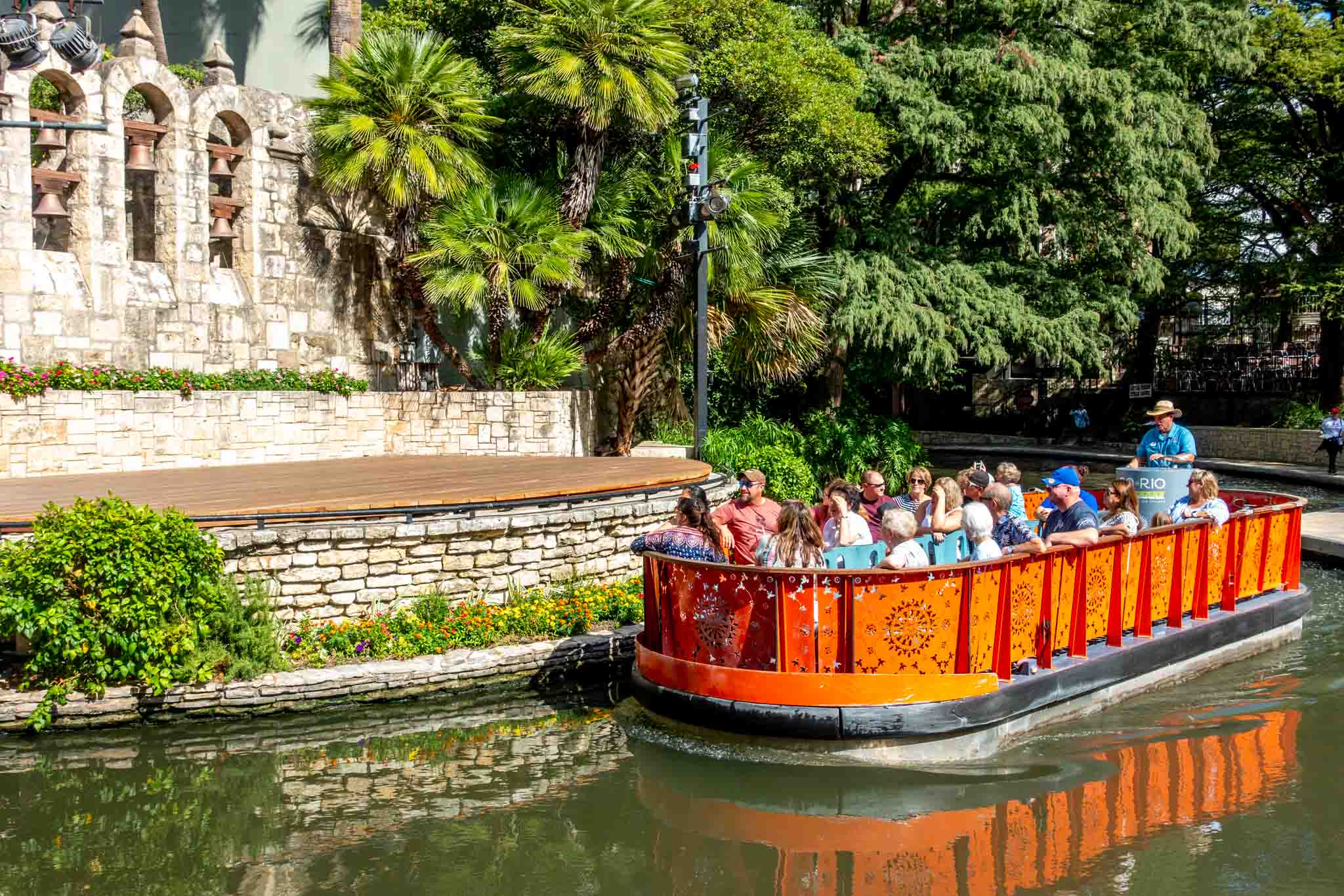 People in an orange barge cruising the river