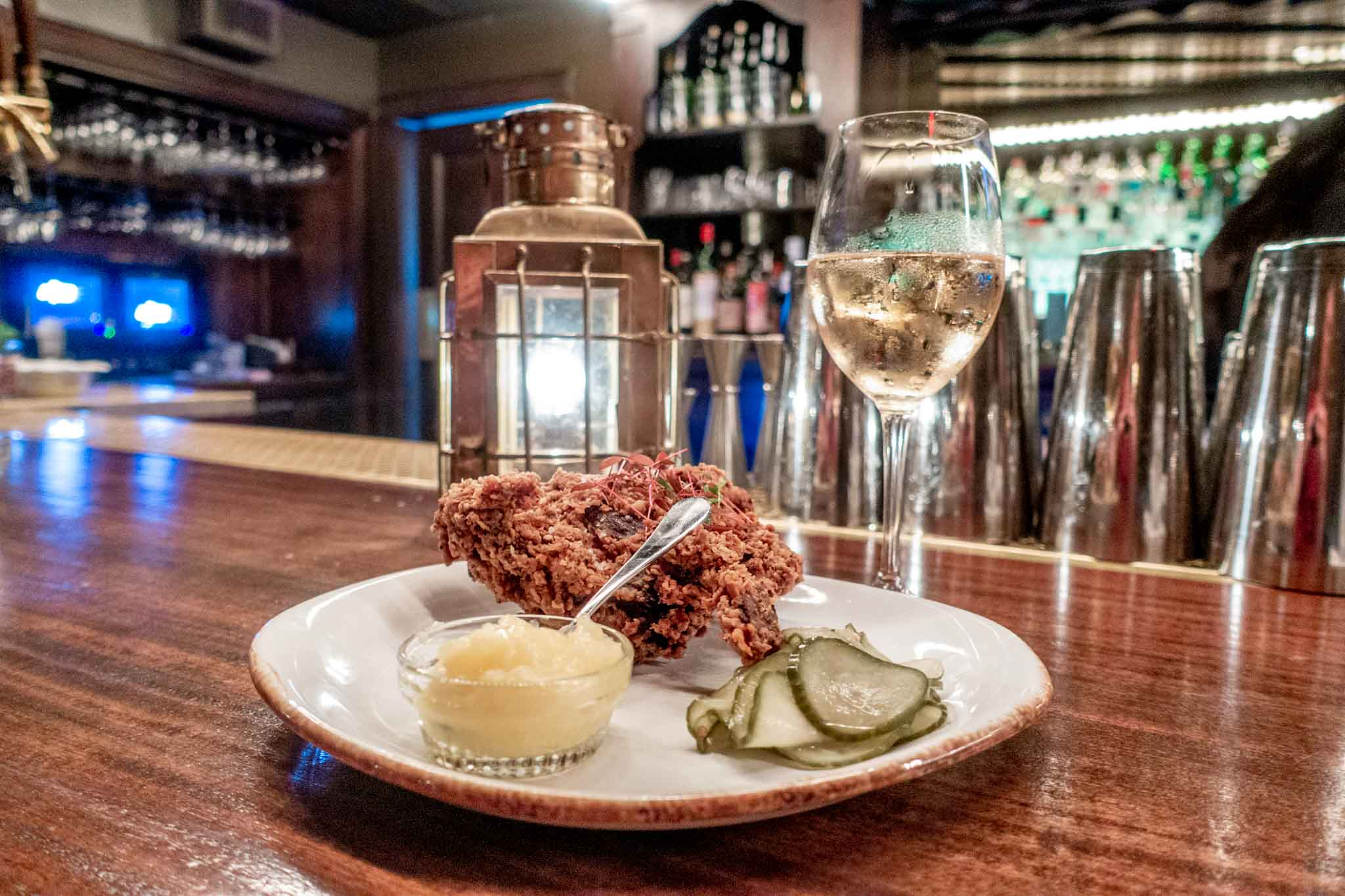 Fried chicken and pickles on a plate with a glass of champagne