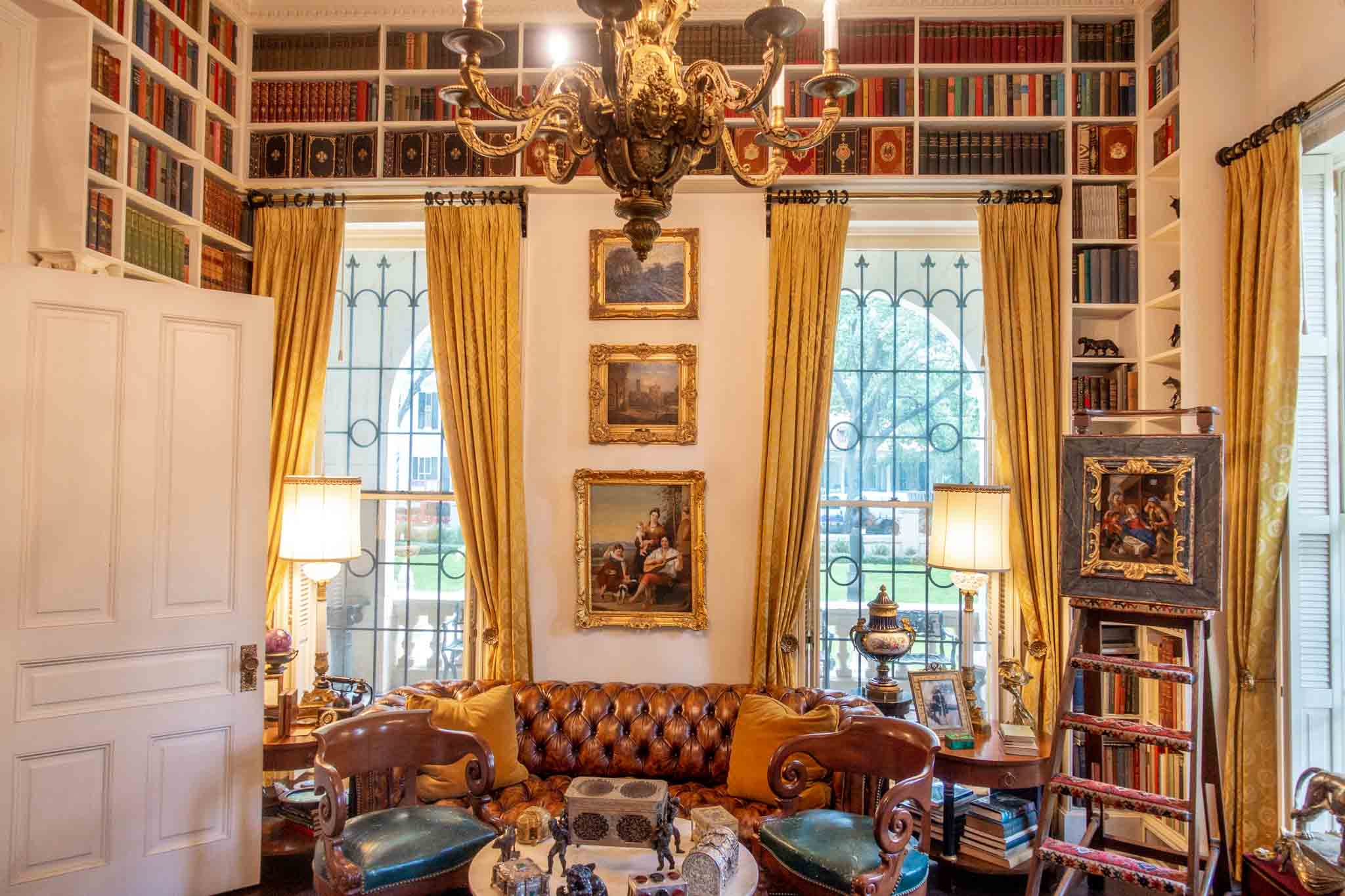Room filled with books and paintings with yellow curtains and a sofa
