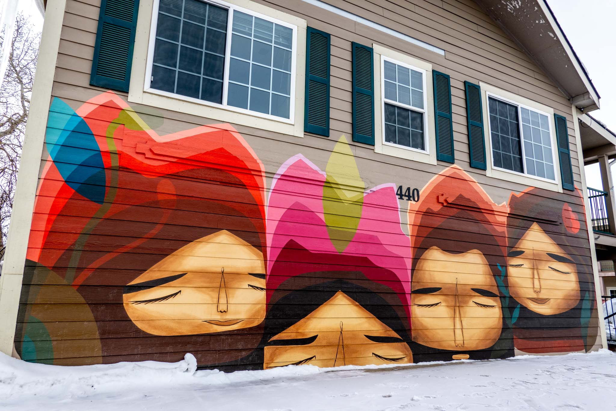 Mural of four heads on side of building