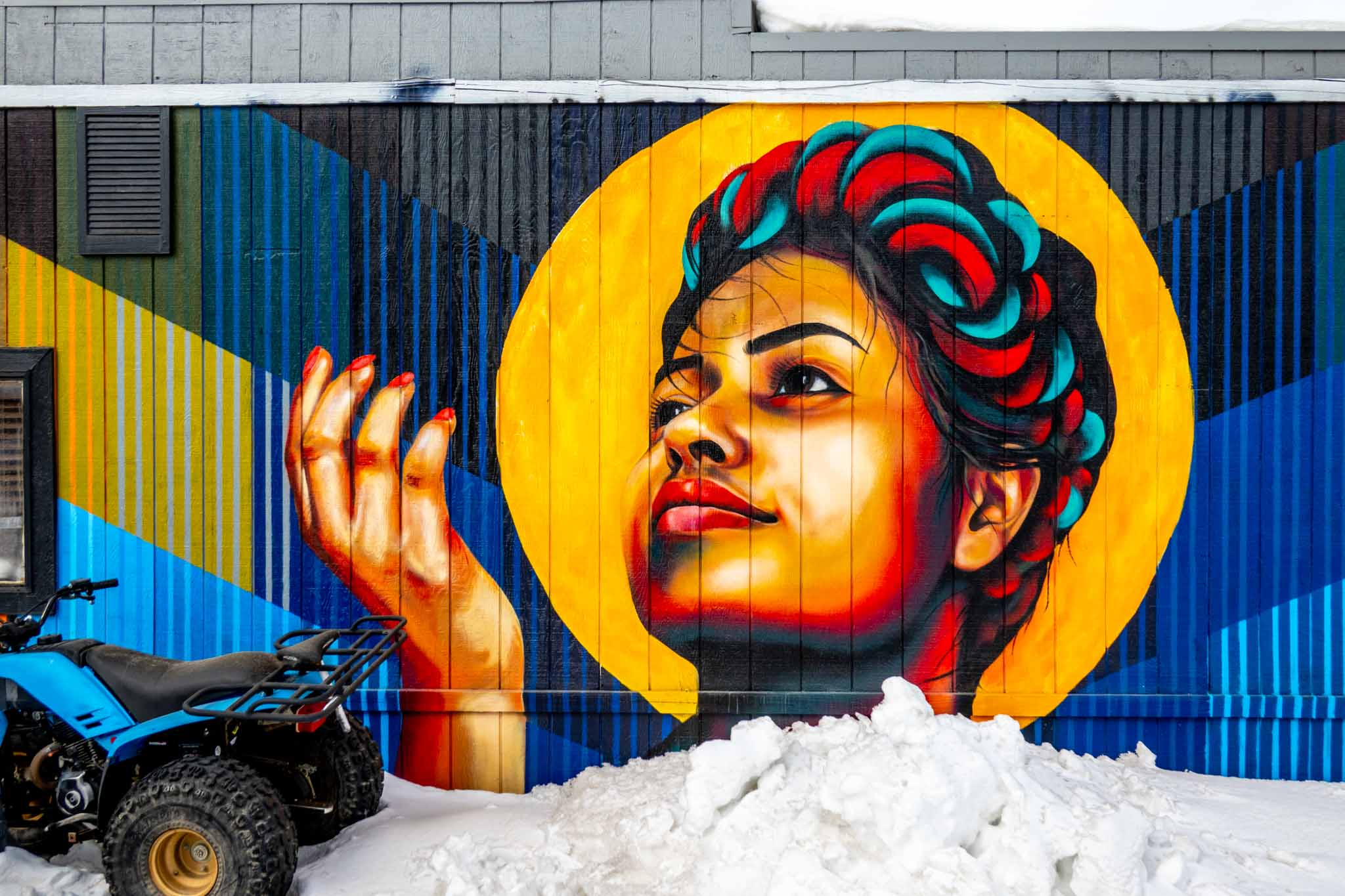 Street art mural of Latina woman on side of building