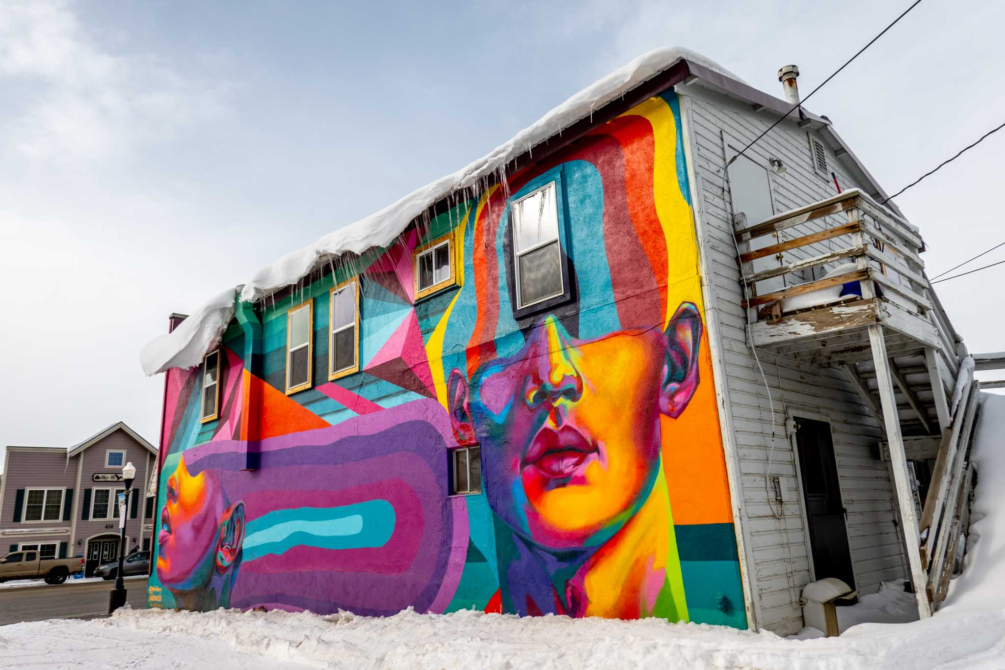 Colorful mural on side of building of two heads