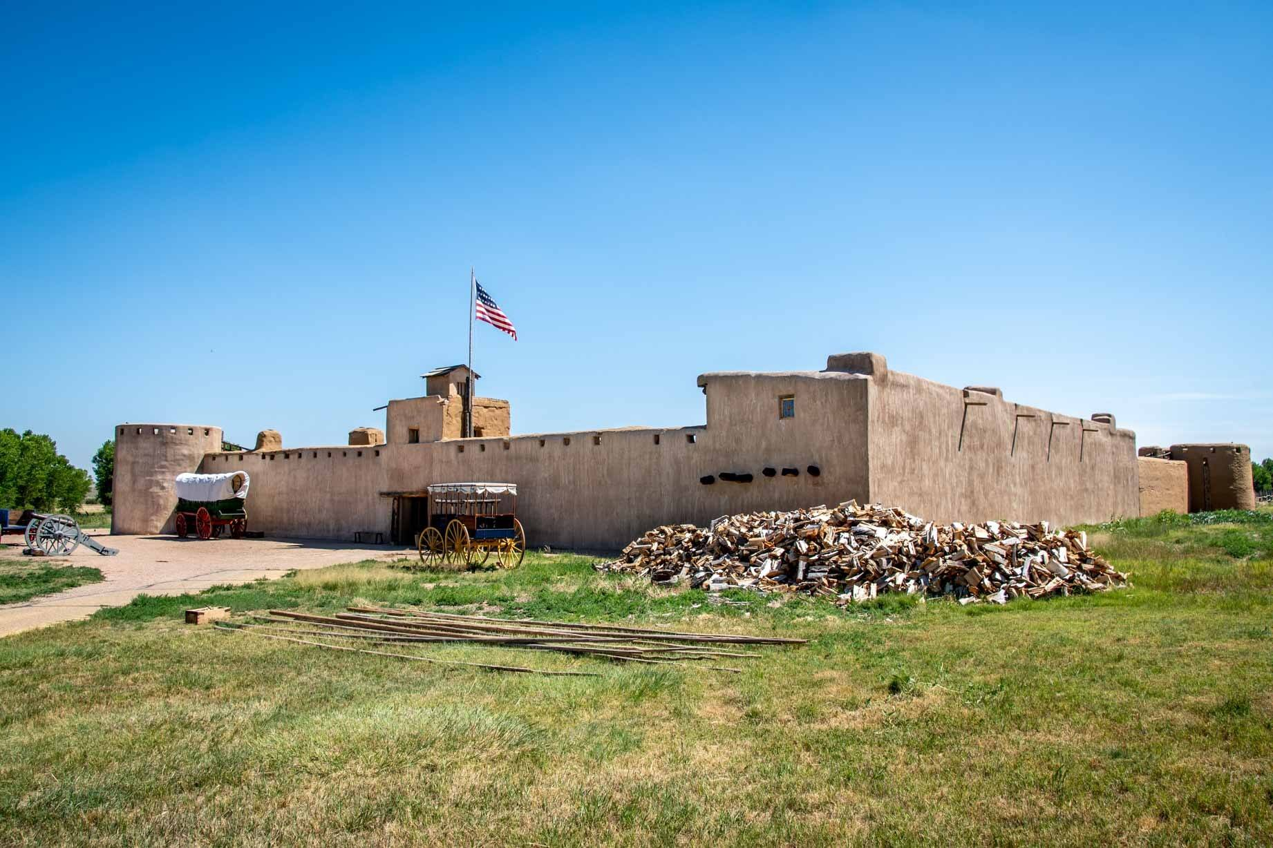 Adobe fort walls with American flag and wagons