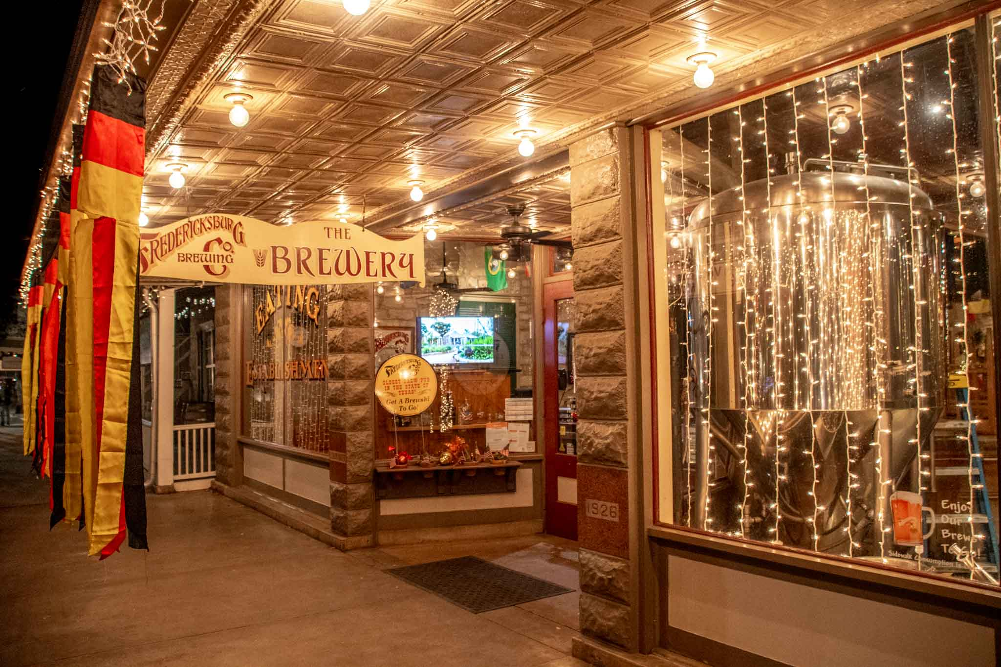 Exterior of the brewery with lights and flags
