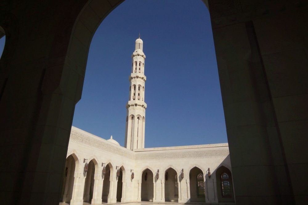 White mosque seen through an archway