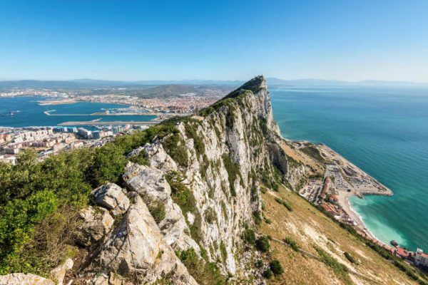Massive rock peak above the ocean with a city below